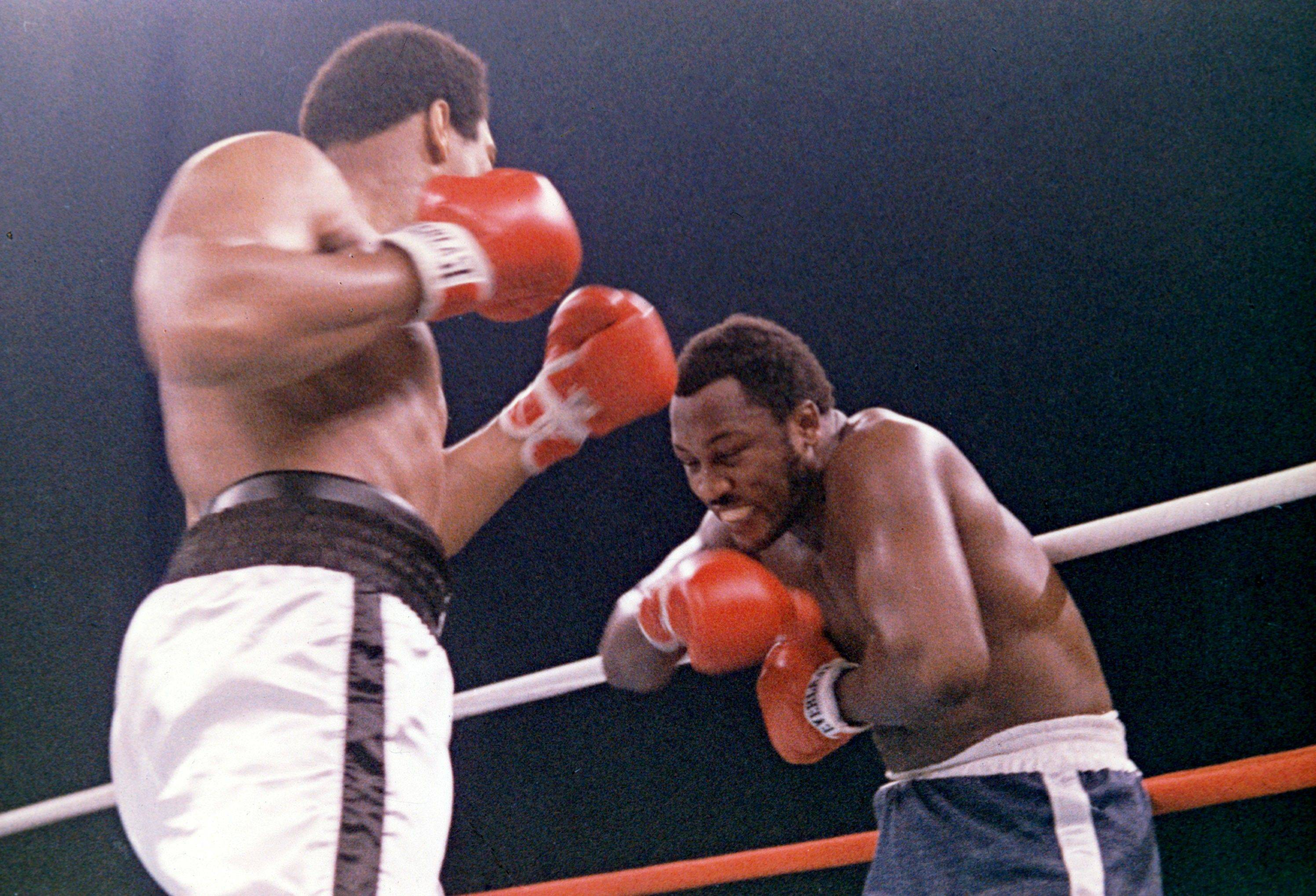 In this Oct. 1, 1975, file photo, heavyweight boxer Joe Frazier grimaces after Muhammad Ali, left, landed a blow to Frazier's head during their boxing bout in Manila, the Philippines. Ali won the fight after Frazier's manager stopped the fight in the 14th round. Frazier, the former heavyweight champion who handed Ali his first defeat yet had to live forever in his shadow, has died after a brief final fight with liver cancer. He was 67. The family issued a release confirming the boxer's death on Monday night, Nov. 7, 2011.