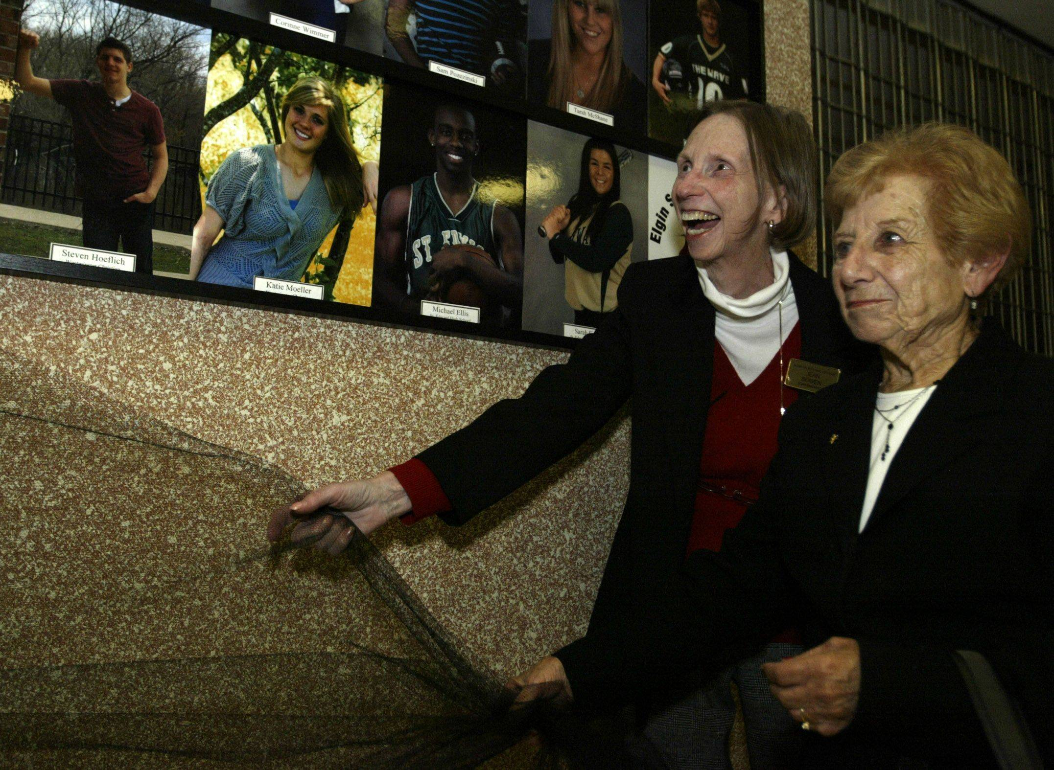 Jean Bowen, left, a member of the Elgin Sports Hall of Fame board of directors, and Helen McCulloch help unveil the new ESHOF's Wall of Fame Sunday at The Centre of Elgin. McCulloch's brother, Vic Masi, has a plaque on the wall for the Masi Serice Awardm which is presented to someone each year who shows pride in the Elgin community.