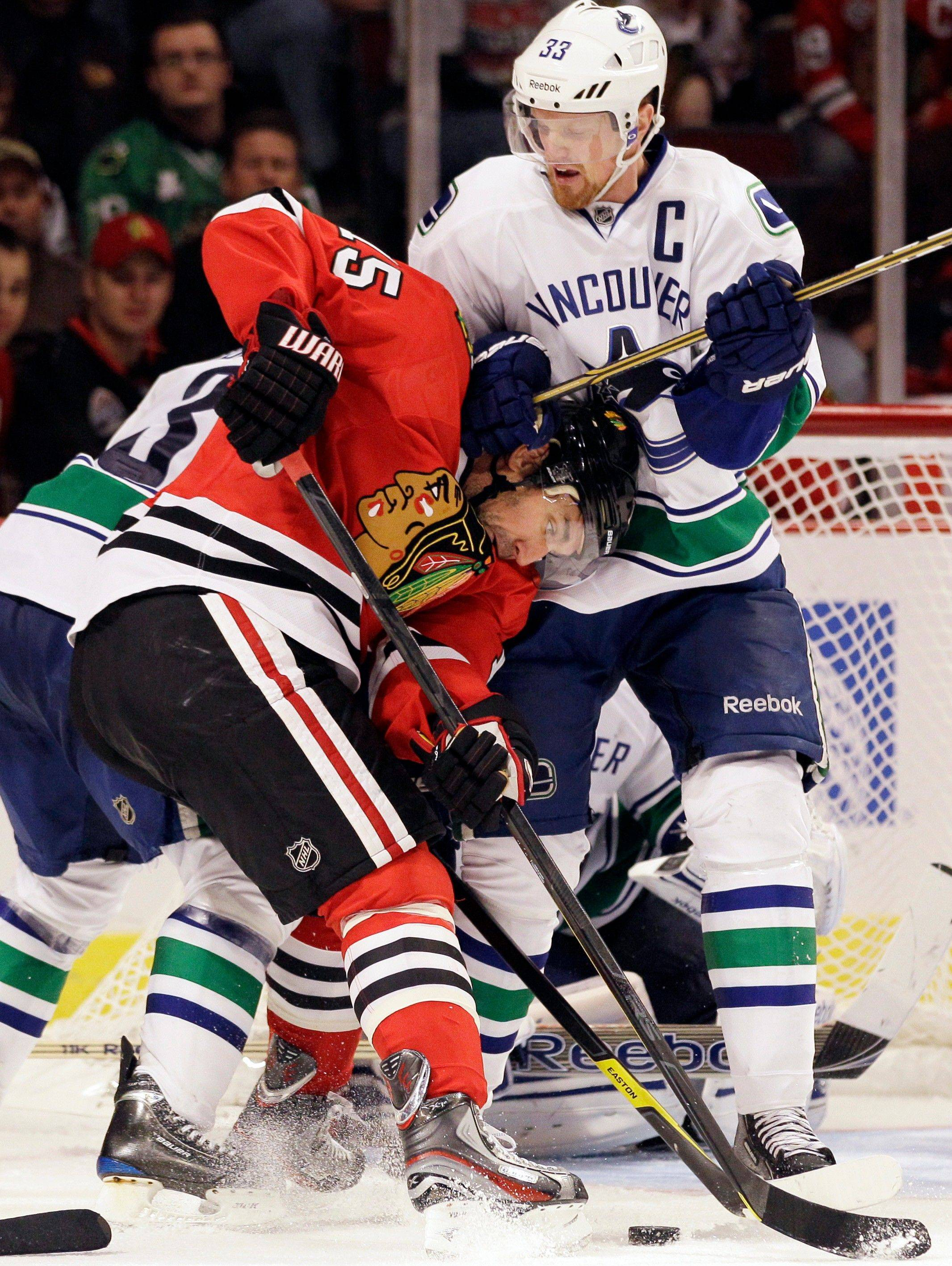 The Canucks' Henrik Sedin and the Blackhawks' Andrew Brunette battle for the puck Sunday night at the United Center.