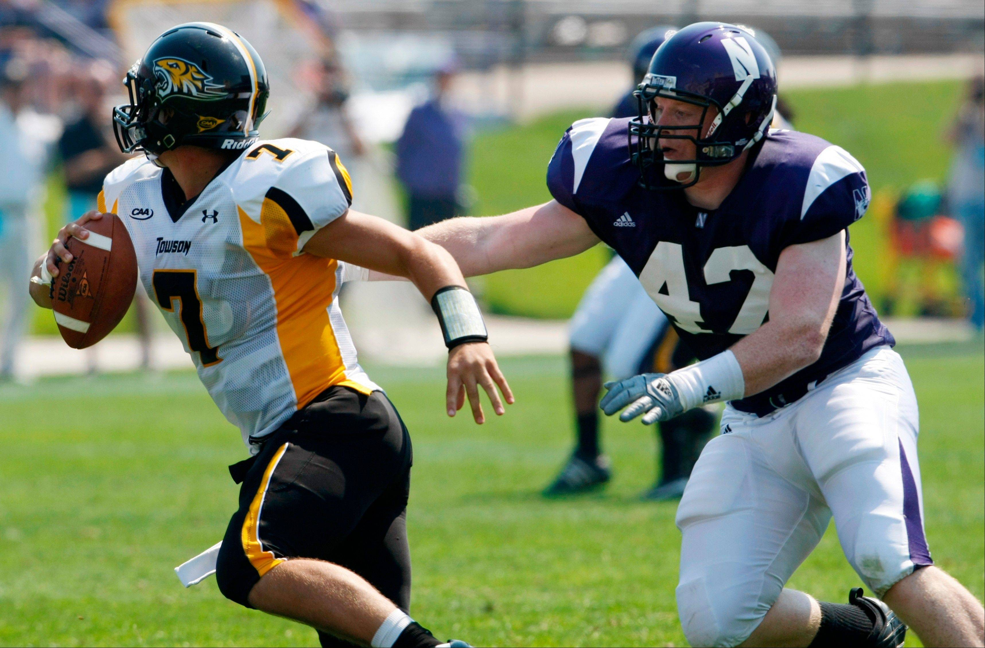 Northwestern's Kevin Watt (42) tries to sack the Towson State quarterback Peter Athens(7) during the second half of an NCAA football game on Saturday, Sept. 5, 2009, in Evanston, Ill.