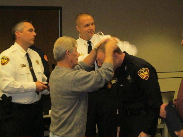 Phil Fleck of Sugar Grove bestows a lifesaving medal on North Aurora Police Officer Ryan McKinness Monday night. McKinness and several civilians are credited with saving Fleck's life. Fleck had a heart attack while driving, passed out and hit a tree Sept. 20.