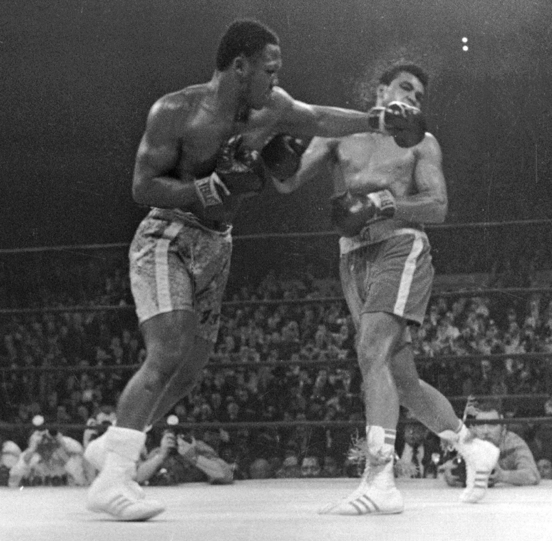 Muhammad Ali, right, takes a left from Joe Frazier during the 15th round of their heavyweight title boxing bout in New York March 8, 1971. Frazier won a unanimous decision. Frazier died Monday after a brief fight with liver cancer. He was 67.