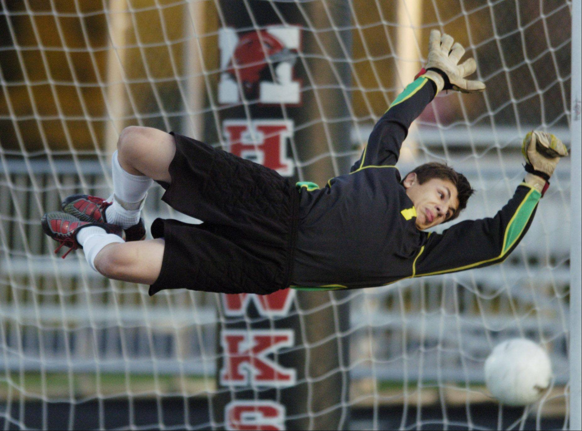 New Trier goalie Tyler Schmarak can't stop the ball kicked by Fremd's Yusuke Kanada during Tuesday's boys soccer supersectional game at Maine South.