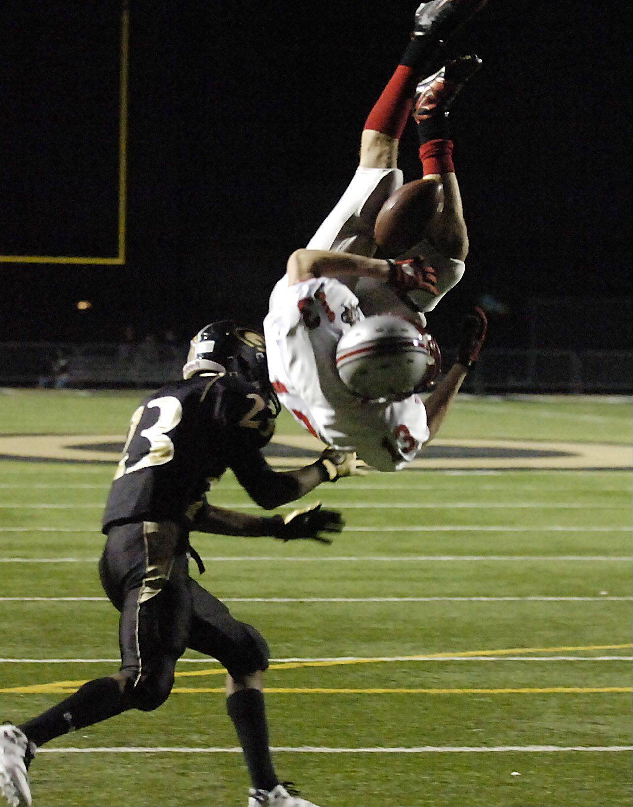 Glenbard North's Tremel Smith upends Palatine's Taylor Hall as he tries to score during the second-round Class 8A playoff football Saturday.