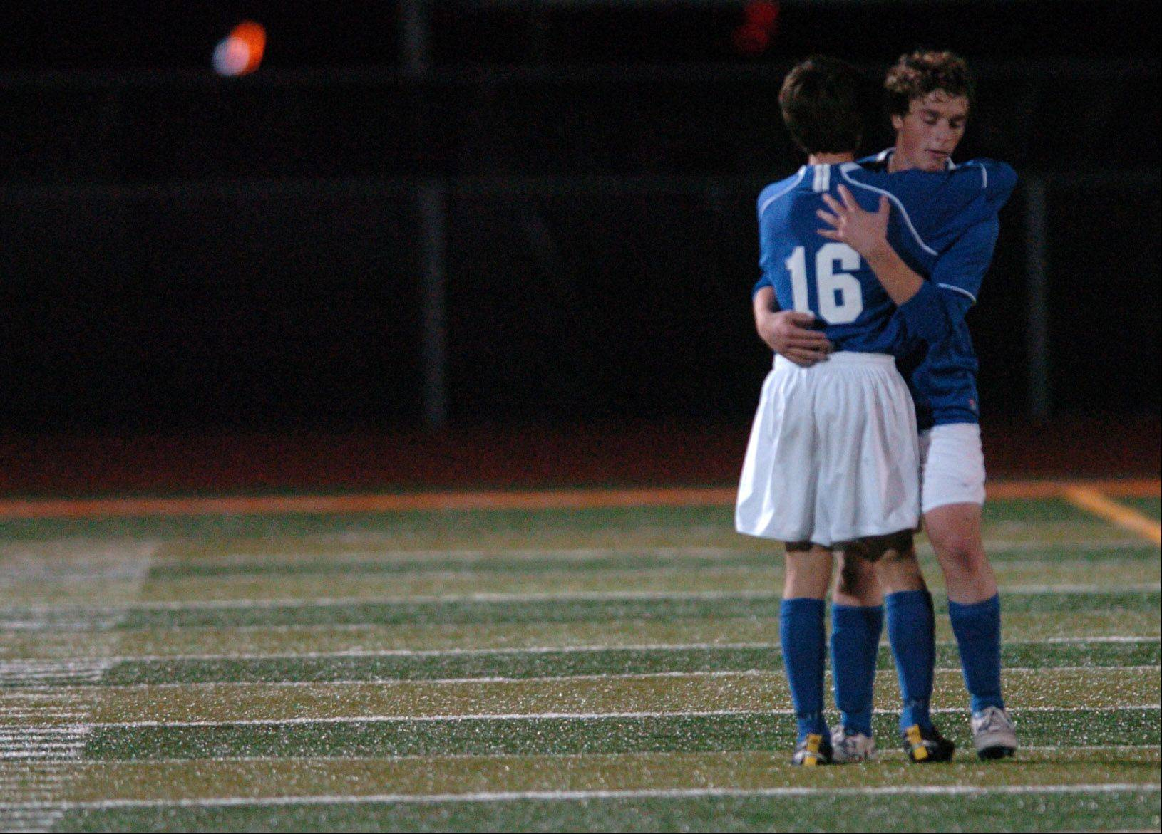 St. Francis' Brett Jungles, 16, hugs teammate Perry Poulos after their loss to Mather Tuesday in the DeKalb supersectional soccer game.