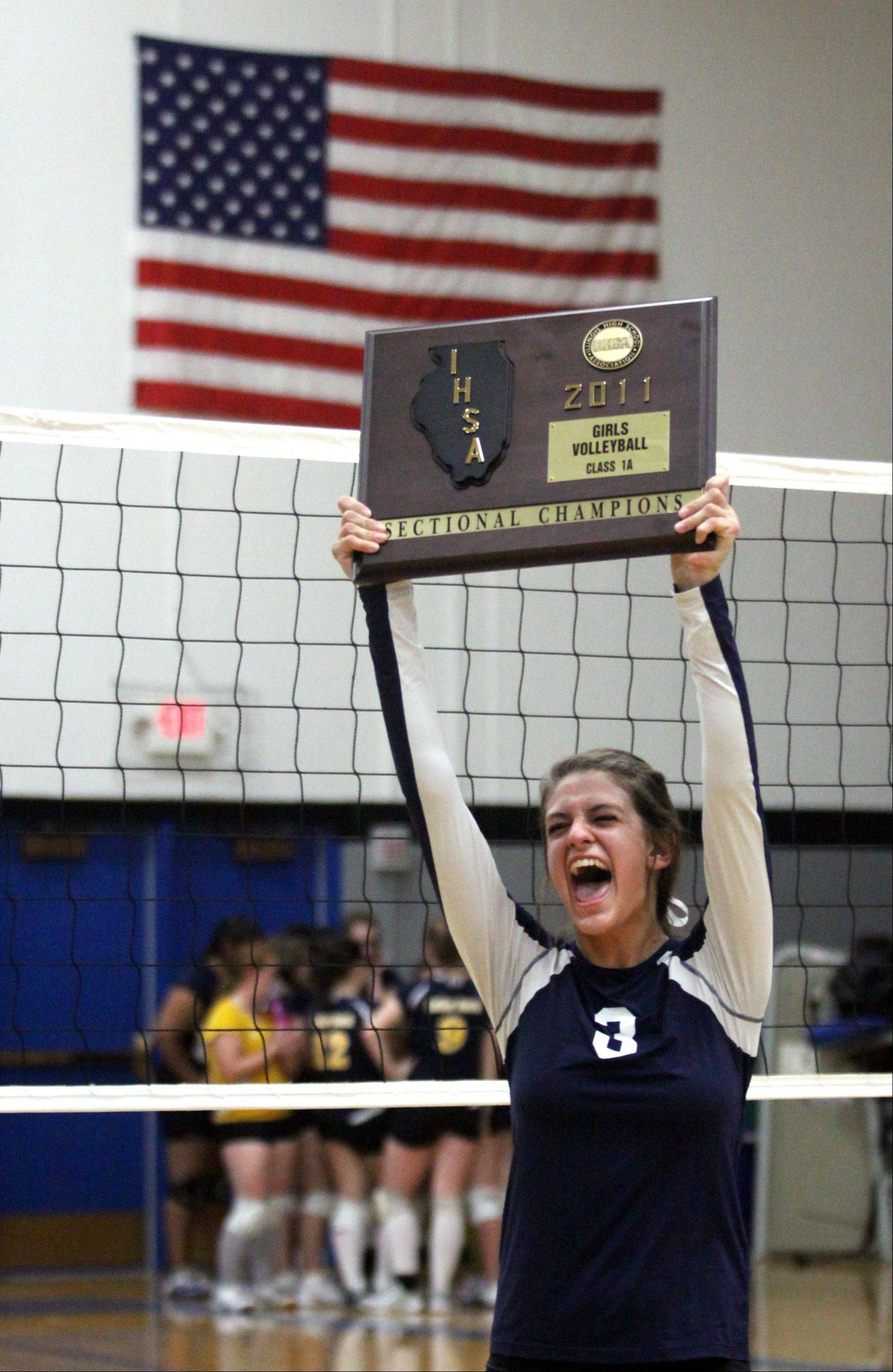 Harvest Christian Academy's Kali Cramer screams with delight as she hoists hardware following a victory over Luther North in Thursday's sectional title match at Westminster Christian School in Elgin.