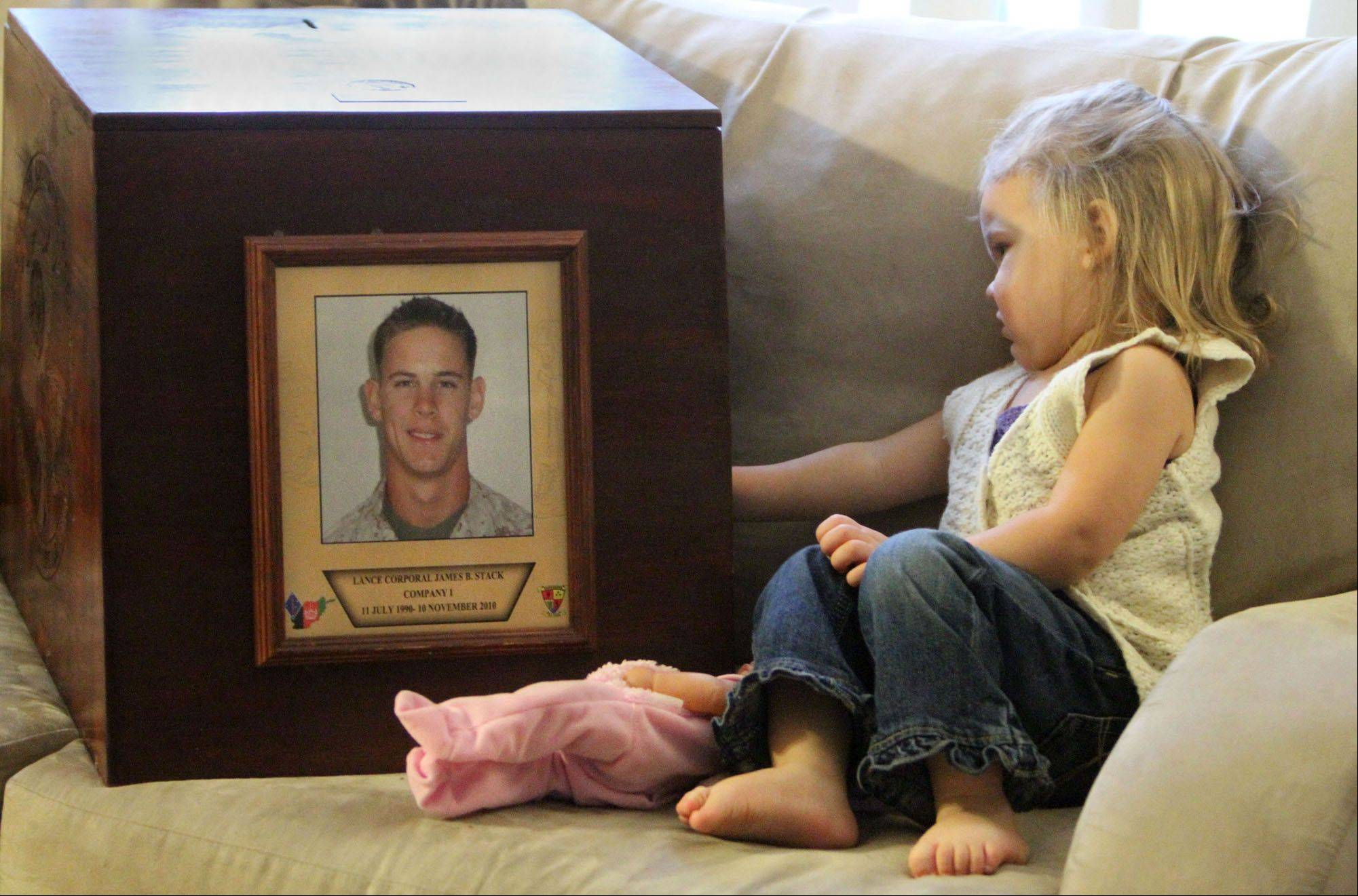 Mikayla Stack sits next to a memorial box madeto honor her father, Marine Lance Cpl. James B. Stack, who died a year ago in Afghanistan's Helmand Province.