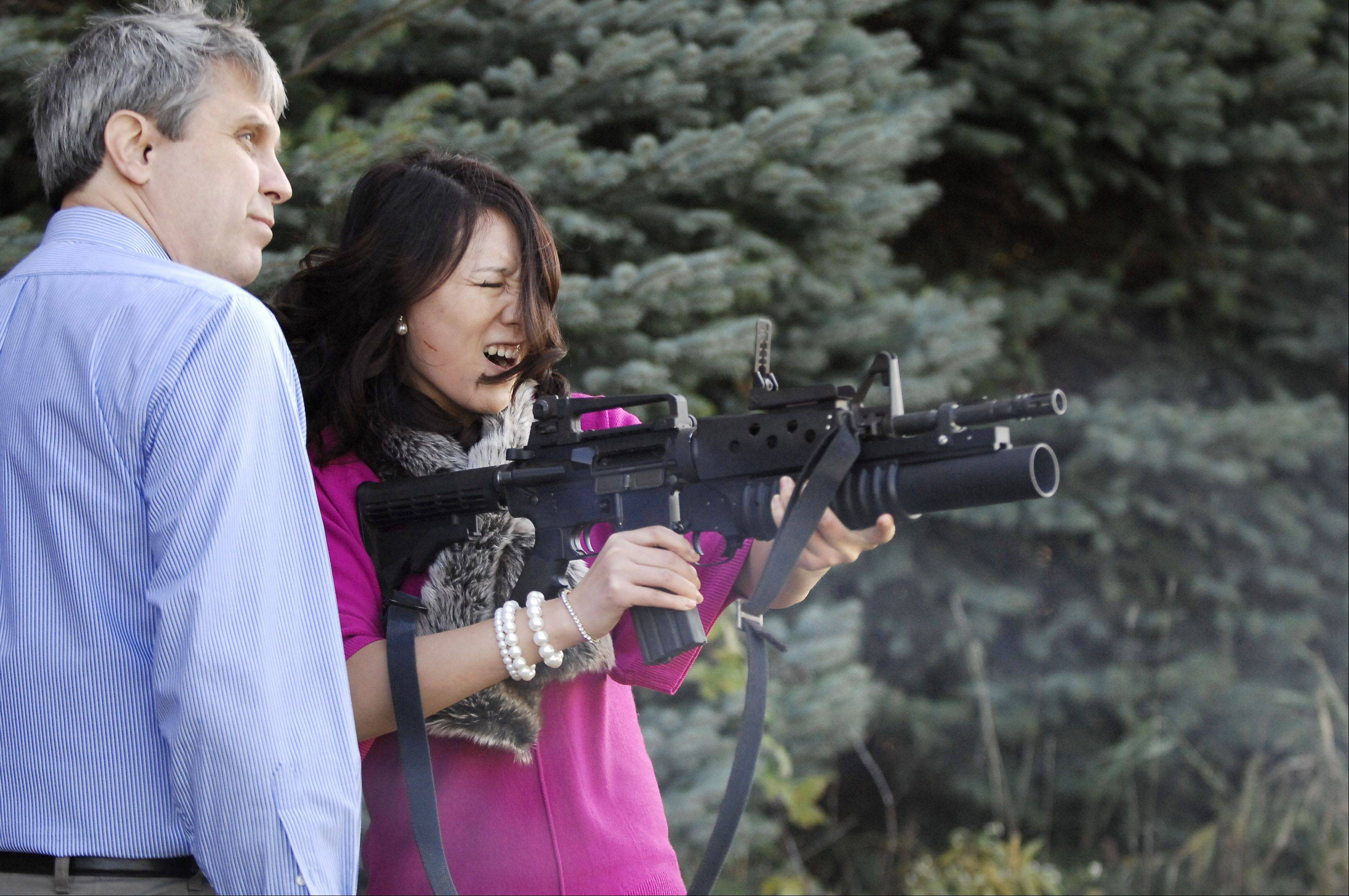Employee Cheng Cheng Zong feels the recoil from the grenade launcher at Airtronic USA.