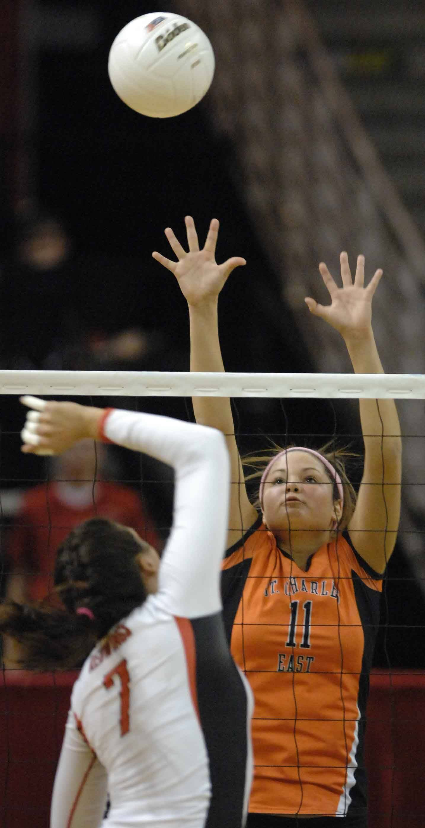 Jenna Jendryk of Benet hits one at Erienne Barry of St. Charles during the Benet vs. St. Charles East girls volleyball 4A semifinal Friday in Normal.