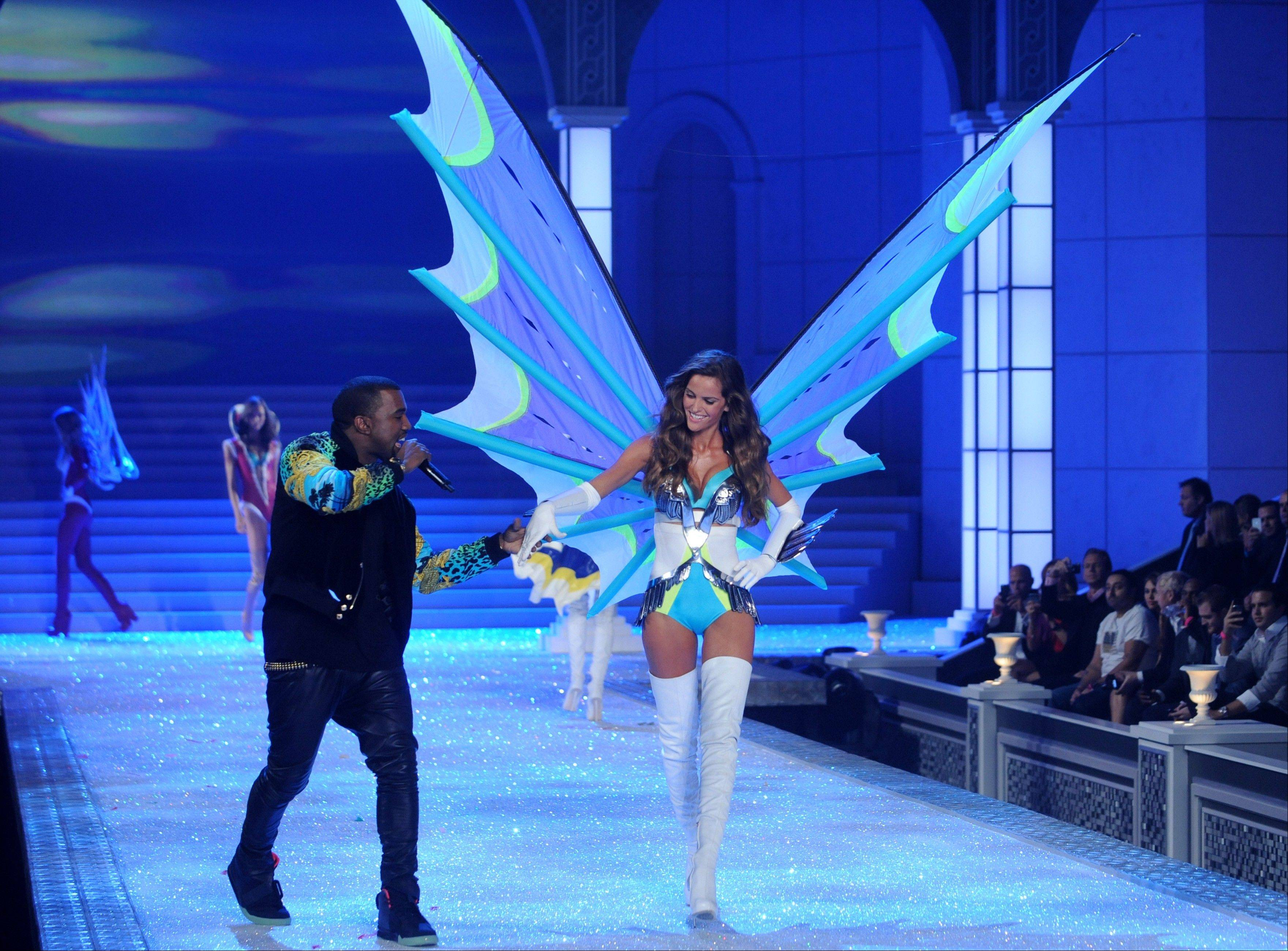 Kanye West holds a model's hand as he performs during the Victoria's Secret fashion show in New York, Wednesday.