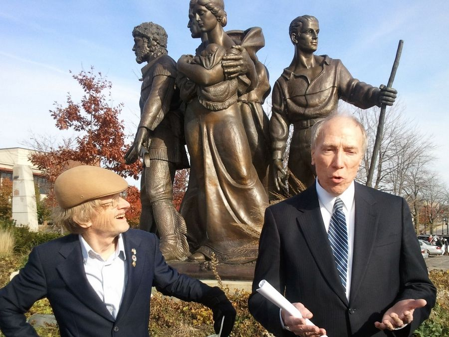 "Steven Youngren, right, shares memories of Trygve Rovelstad's ""Pioneer Family Memorial"" sculpture, which was rededicated Saturday in Elgin. Youngren was president of the Pioneer Memorial Foundation of Illinois, which raised money for the memorial. Roger Bear, left, was the foundation's vice president."