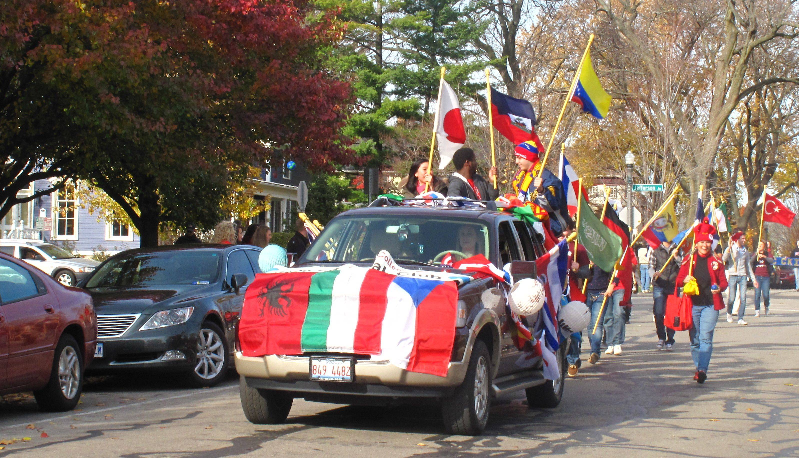 Members of North Central College's International Club walk down Brainard Street during the school's Homecoming parade Saturday.