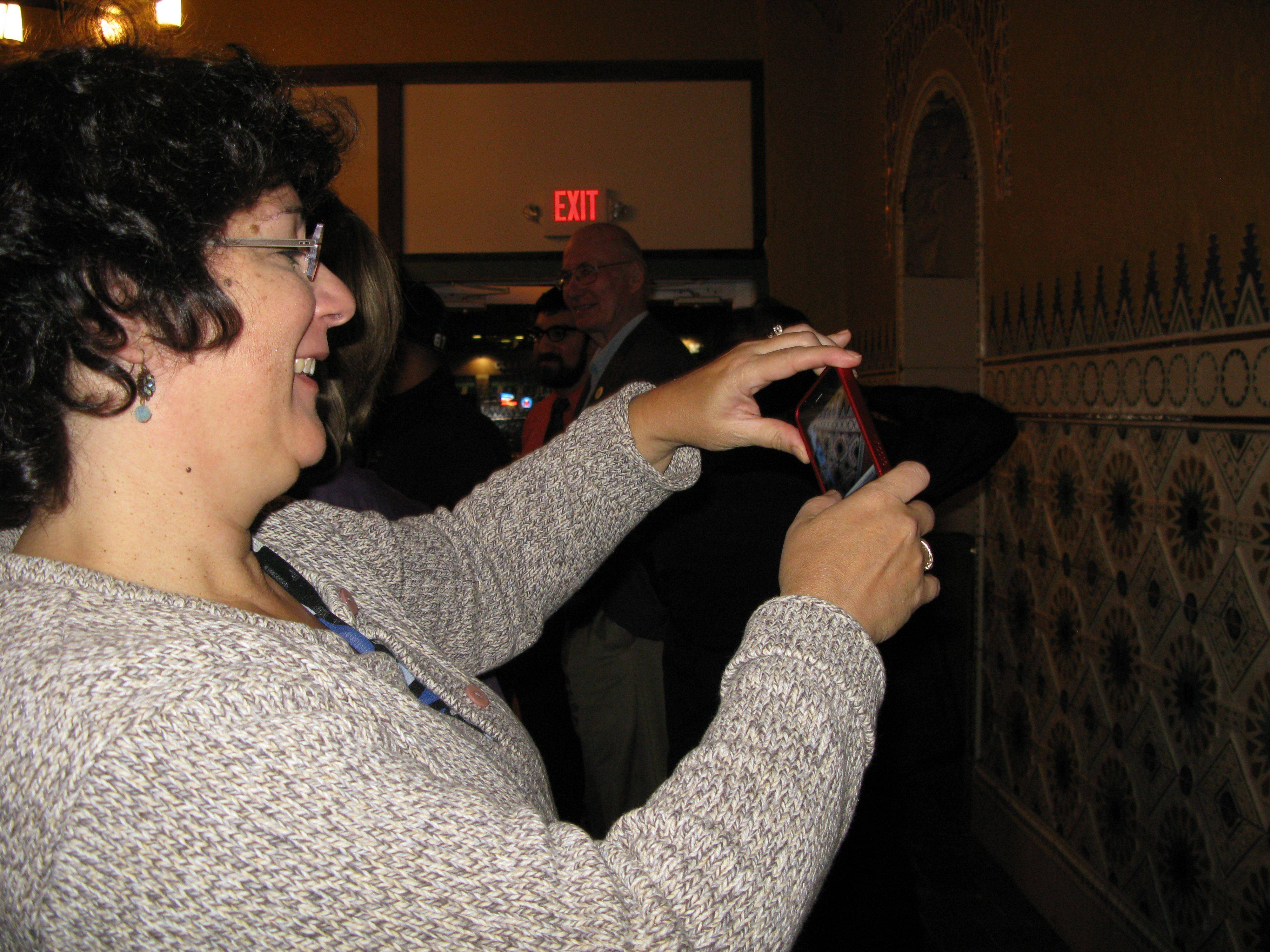 Lauren Wolf, one of the volunteers who helped with the Des Plaines Theatre's restoration, takes pictures of the terra cotta tiles in the renovated theater's lobby Friday during the grand reopening.