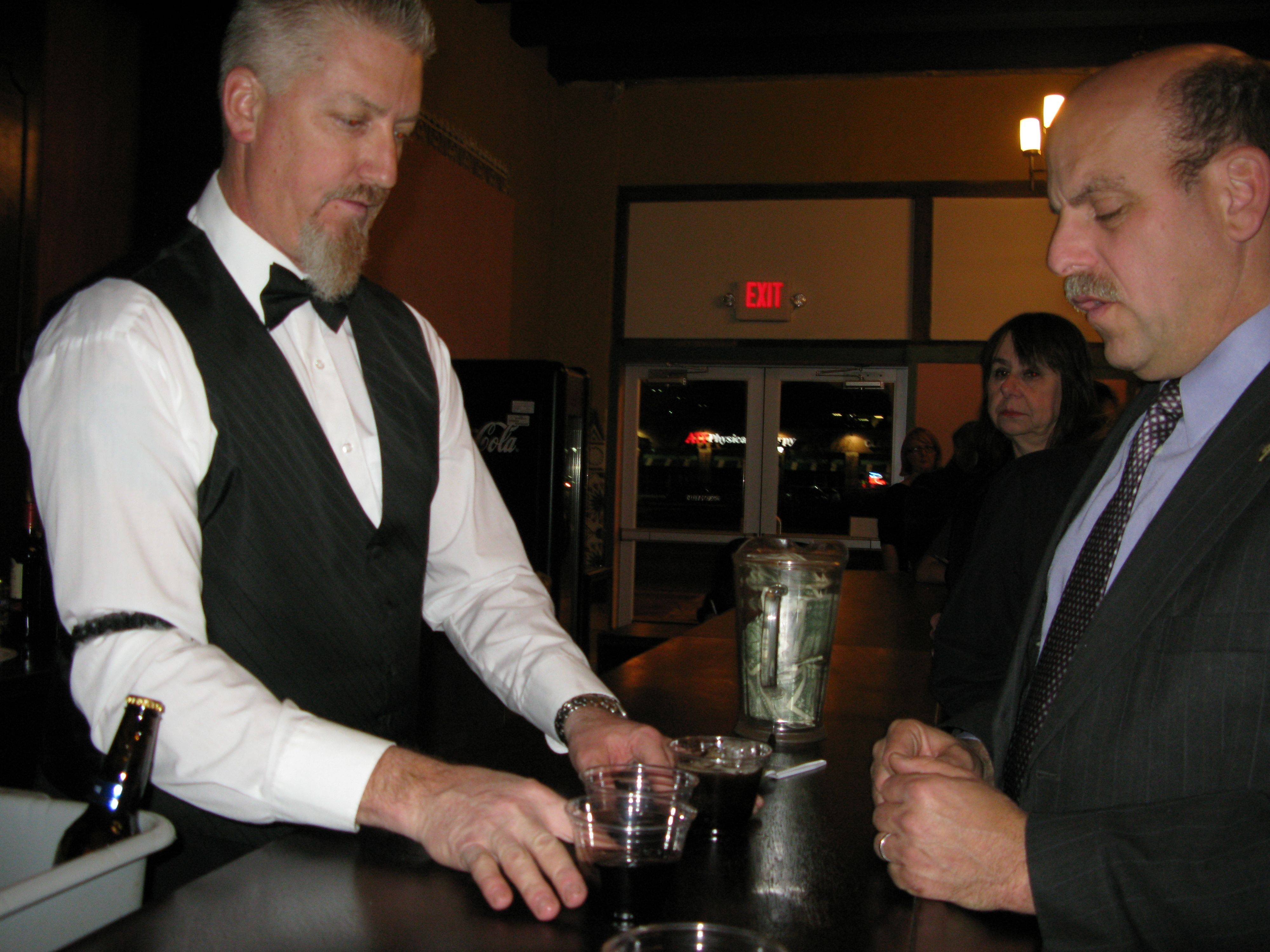 Bartender Jeff Weber serves a drink to Des Plaines Fire Chief Alan Wax at the downtown Des Plaines Theatre's grand reopening Friday.