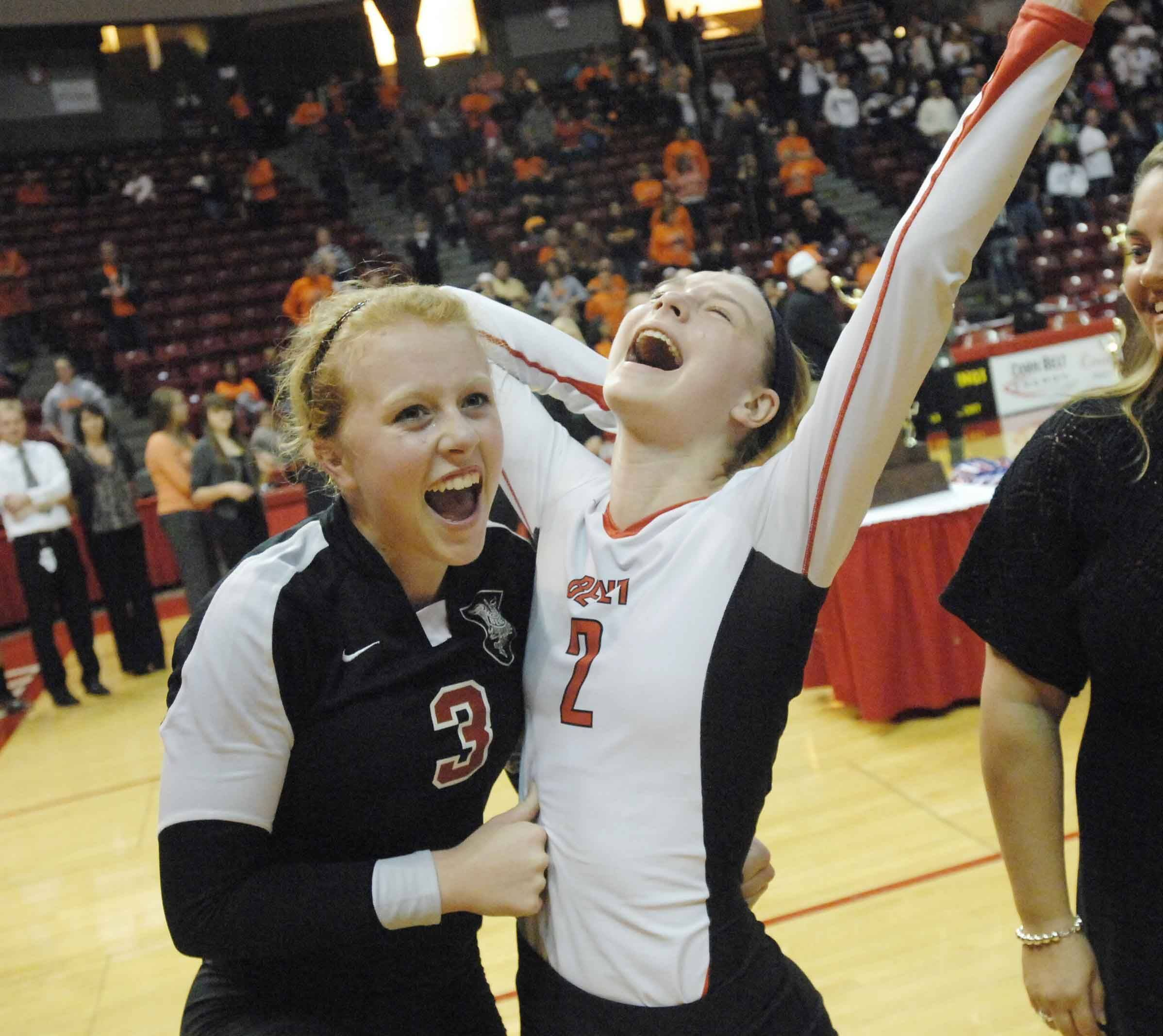 Benet's Sheila Doyle, left, and Brittany Kmieciak celebrate the Redwings' win over Cary-Grove in the Class 4A volleyball championship in Normal Saturday.