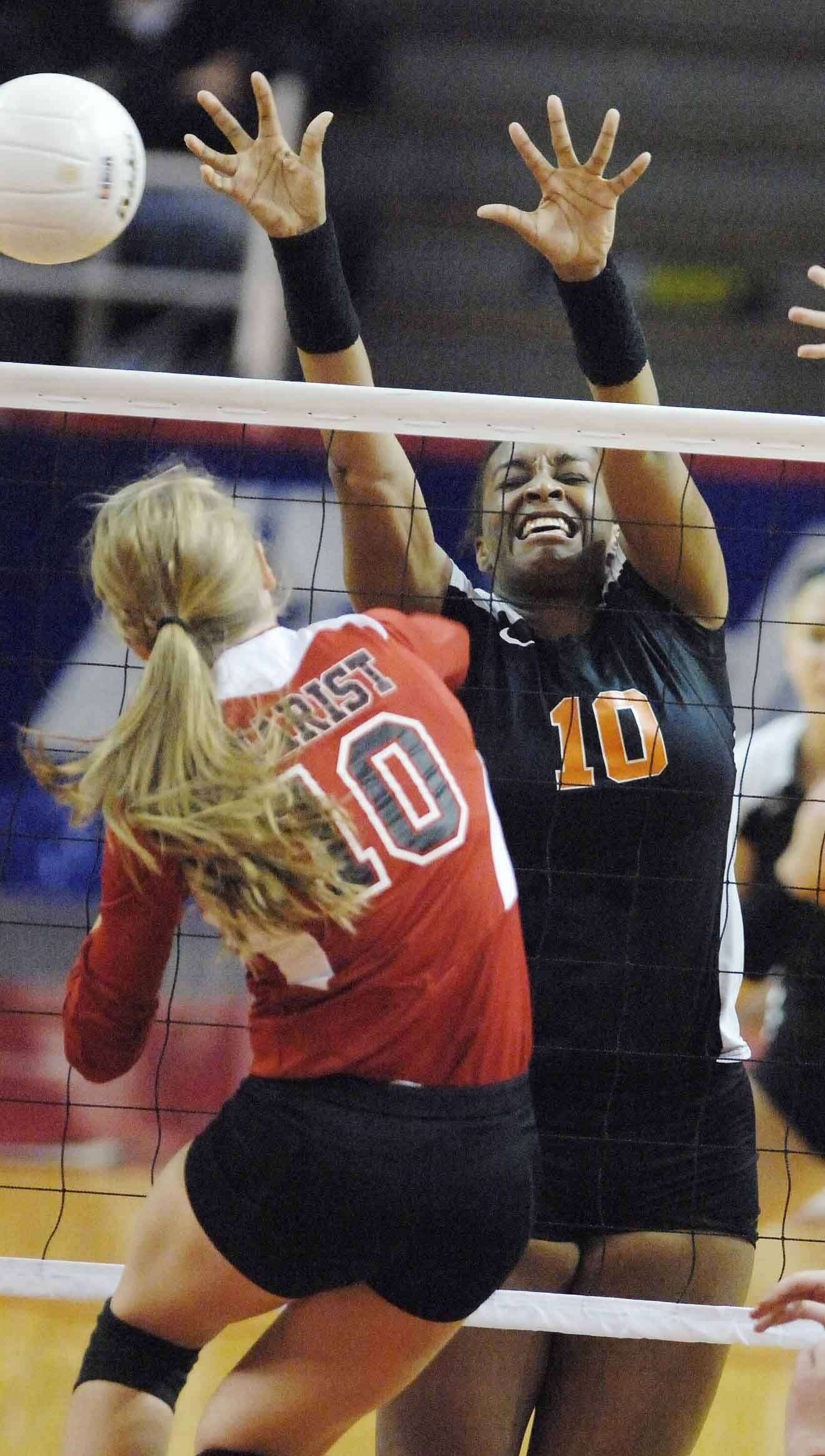 Nicole Lambert of St. Charles East goes up for a block during the third-place match against Marist Saturday night in Normal.