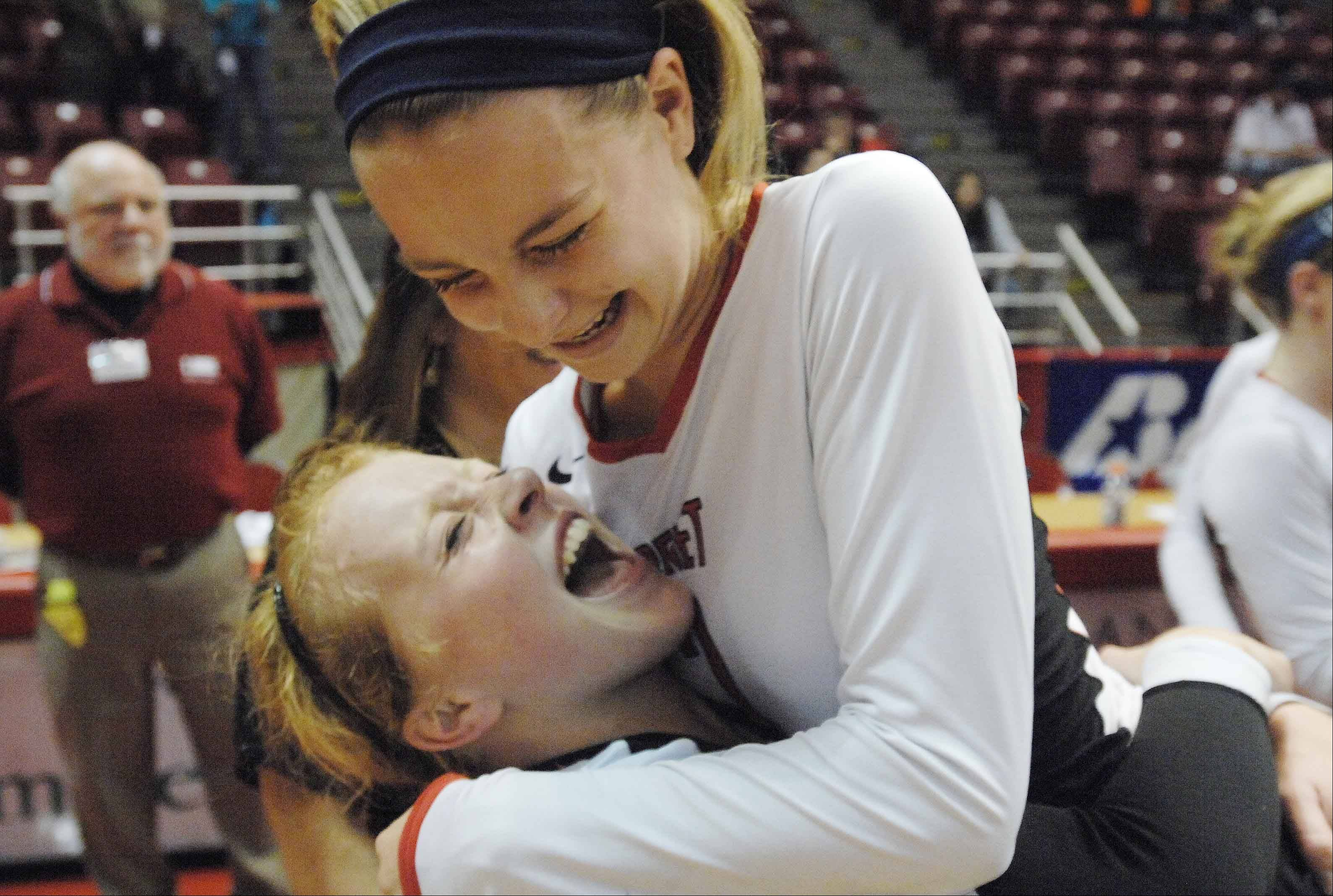 Shelia Doyle and Brittany Kmieciak hug after beating Cary-Grove in the Class 4A volleyball championship in Normal Saturday.