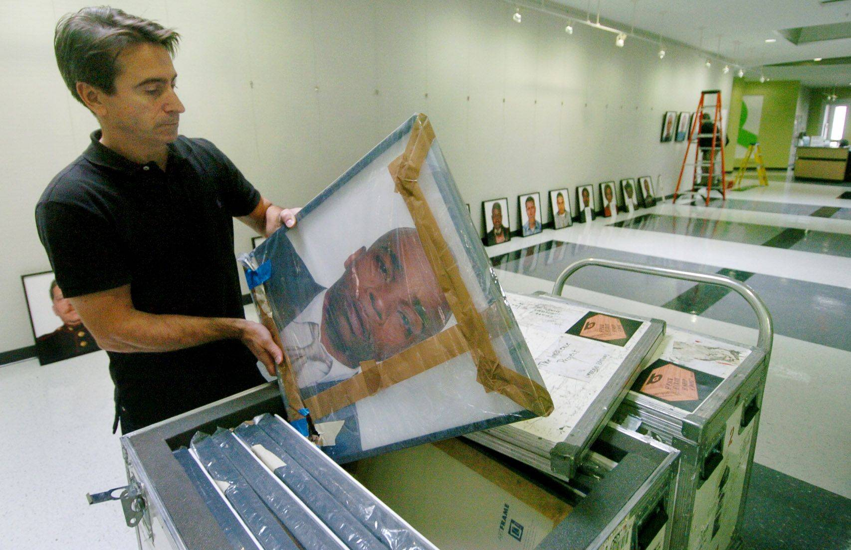 "Mike Ensdorf, professor of communications at Roosevelt University, unpacks an exhibit of photos of wrongfully convicted Americans called ""The Innocents: Headshots,"" that will be on display beginning today through January 13 at the college's Schaumburg campus."