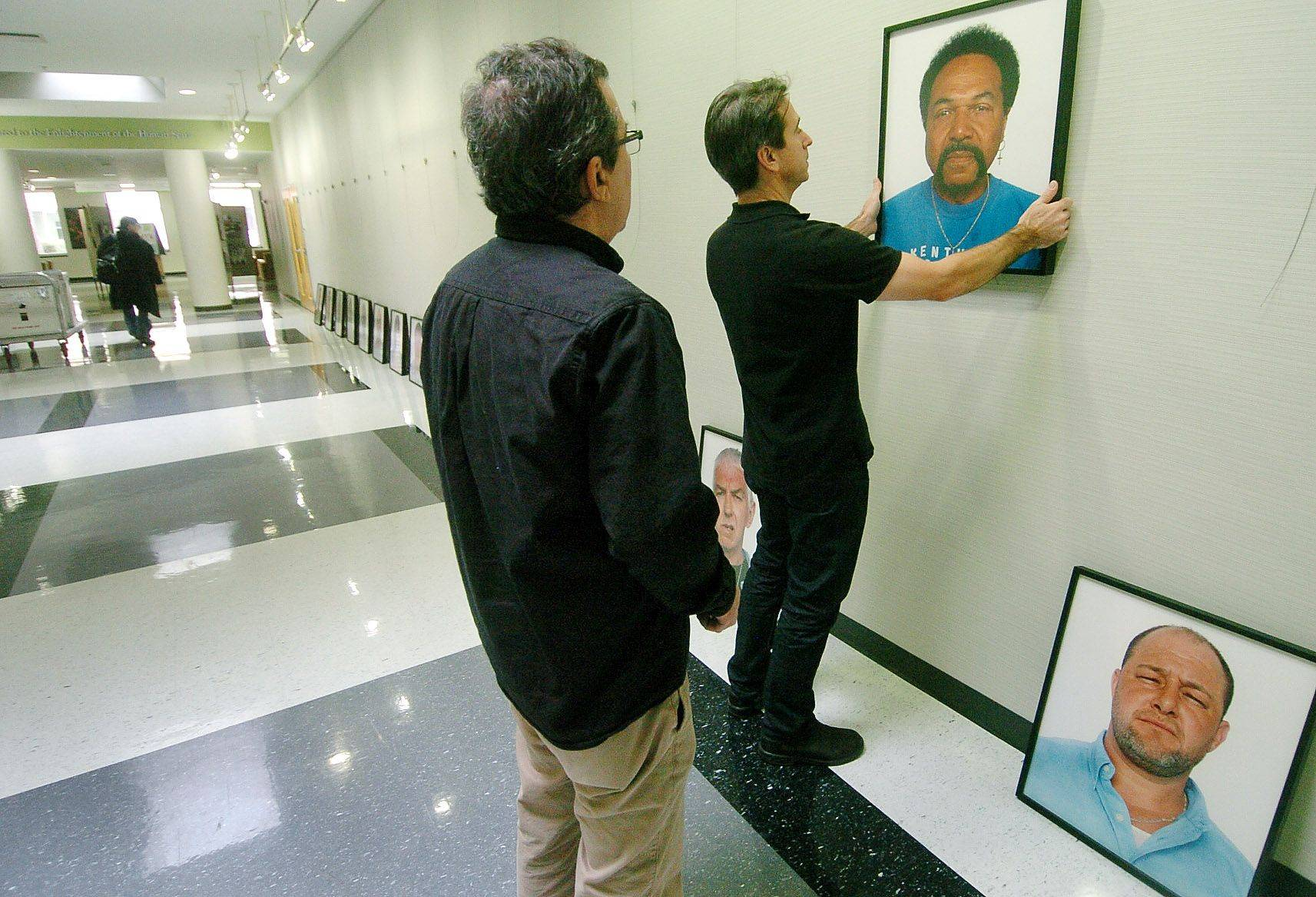 "Mike Ensdorf, professor of communications at Roosevelt University, right, and exhibit designer John Hilarides, prepare an exhibit of photos of wrongfully convicted Americans called ""The Innocents: Headshots,"" that will be on display beginning today through January 13 at the college's Schaumburg campus."