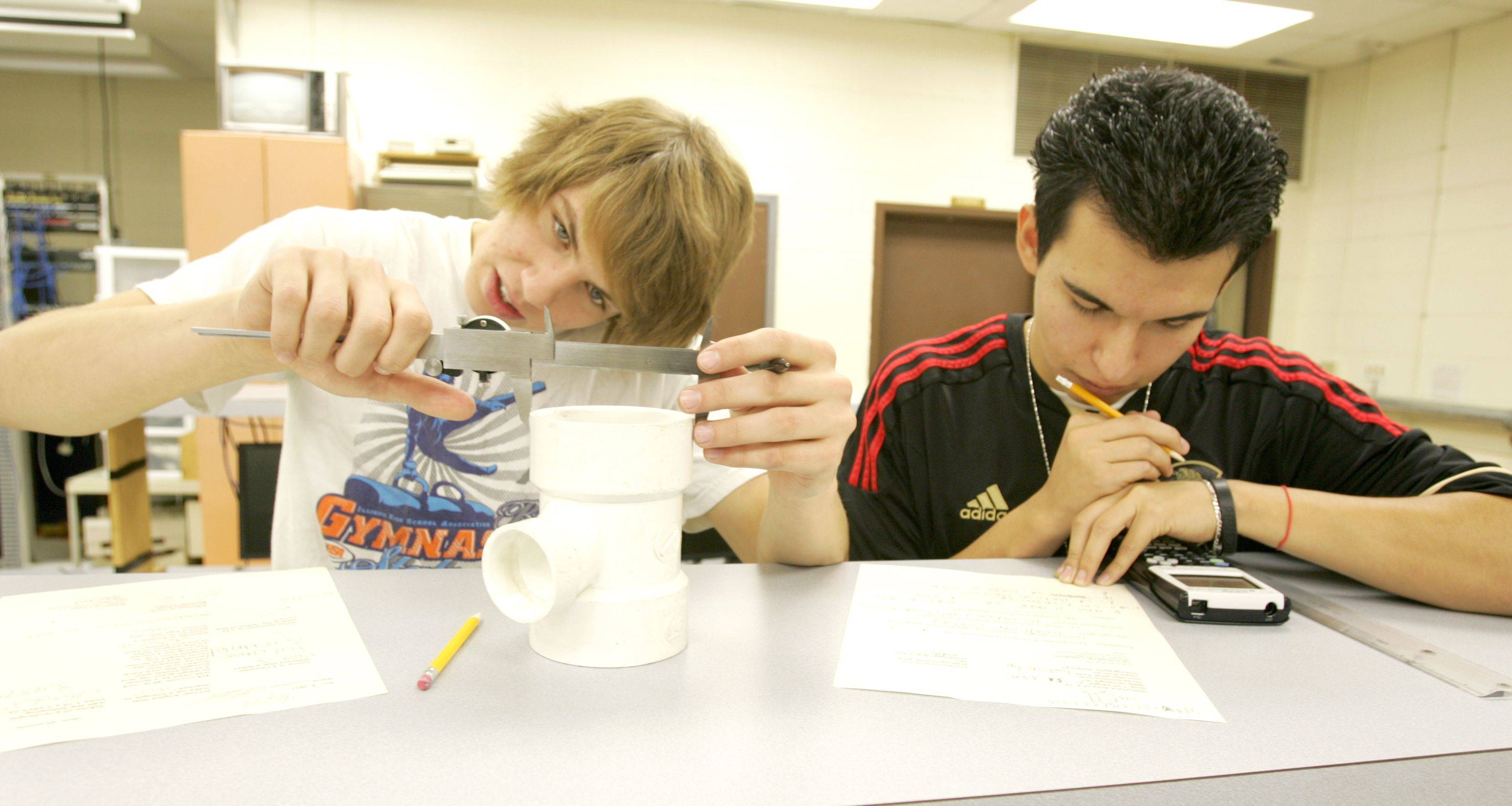 Norman Vitellaro III, left, measures diameter and height to find volume and surface area in his introductory engineering class at Fenton High School in Bensenville with Alejandro Mora Jr.