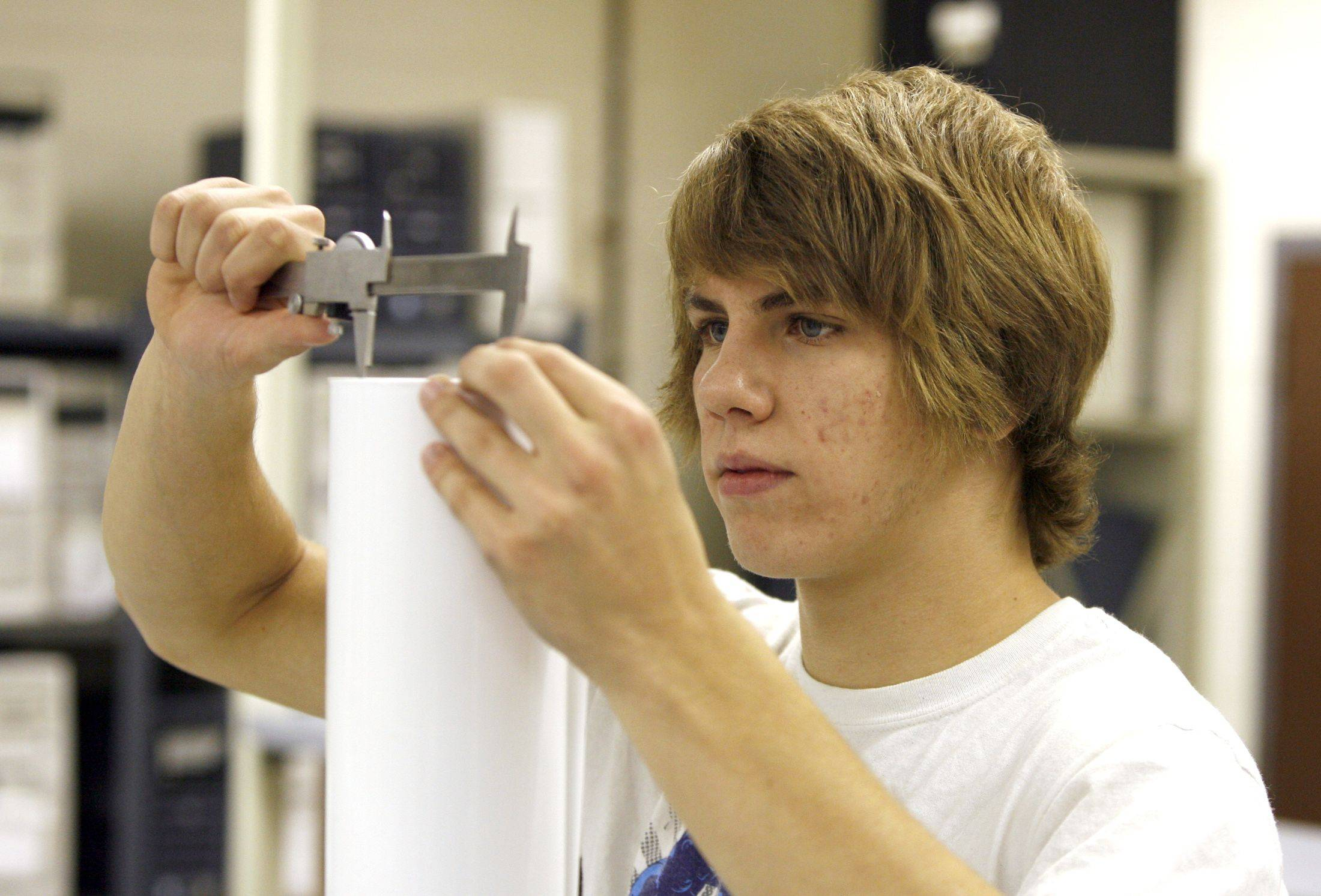 Norman Vitellaro III measures diameter and height to find volume and surface area in his introductory engineering class.
