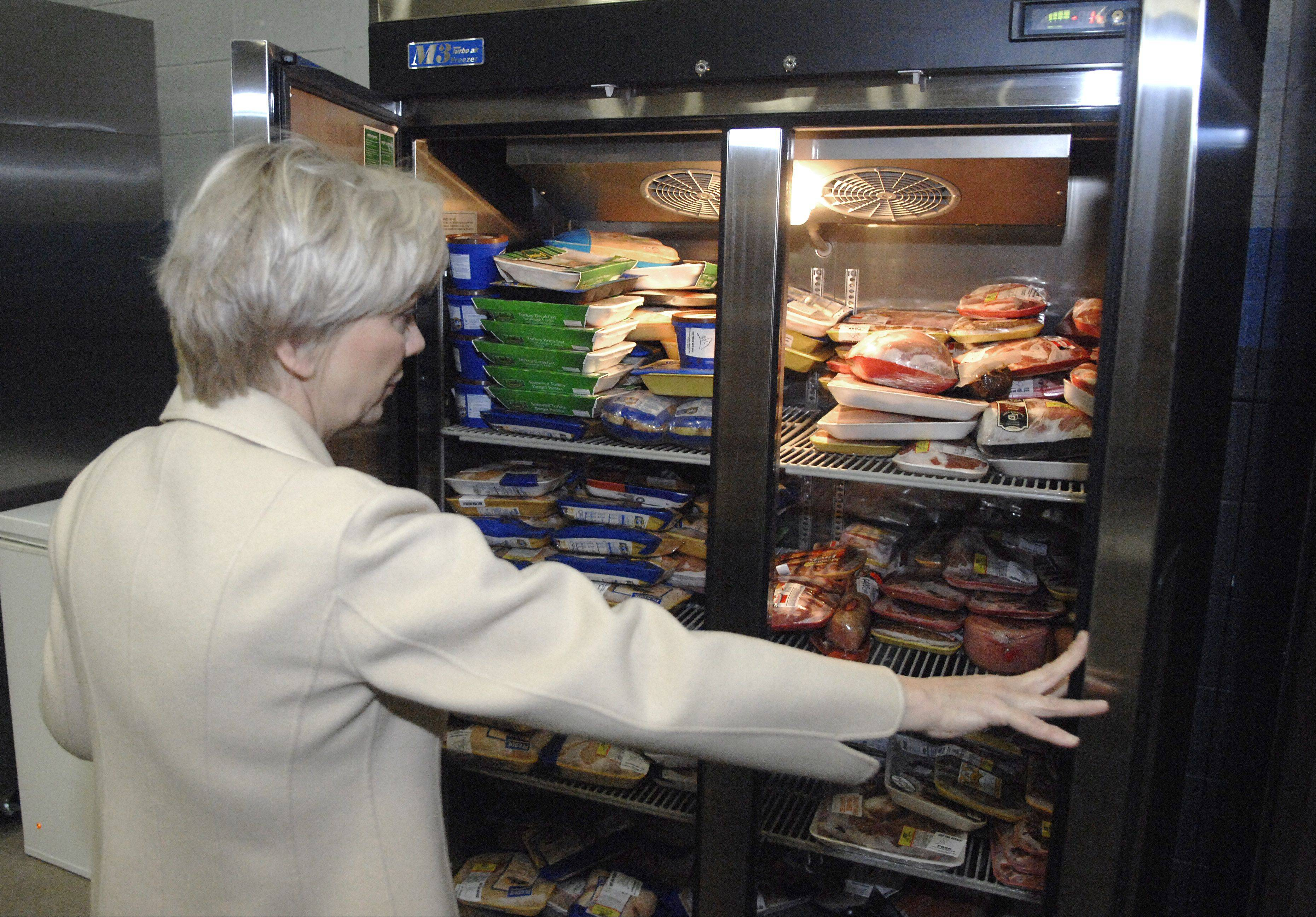 Feeding Greater Elgin Executive Director Susan Ericson shows where meat is stored in one of the freezers in the nonprofit's new warehouse at 1553 Commerce Drive. A grand opening is set for Dec. 3.