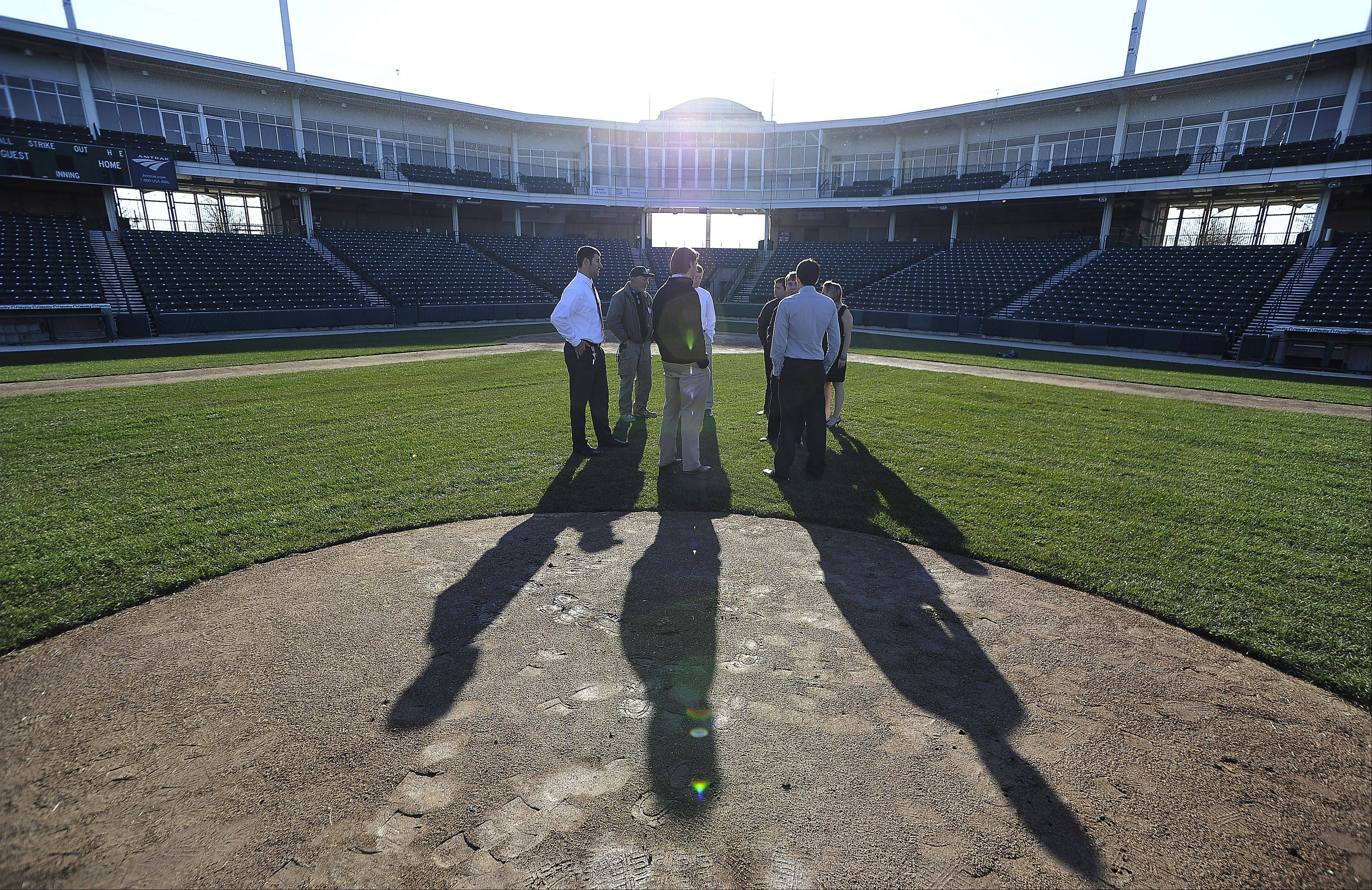 Andy Viano, president and general manager of the Schaumburg Boomers baseball team, and other personnel take the field looking over the new turf grass at the stadium.