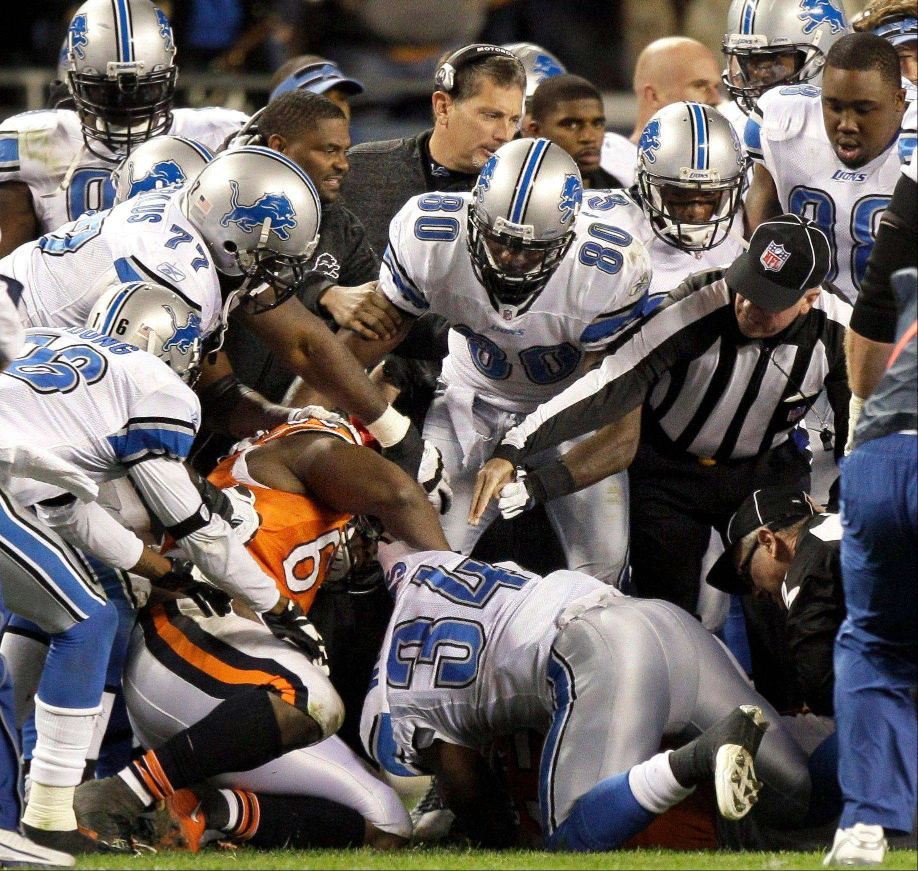 Officials break up a fight between Chicago Bears and Detroit Lions players in the second half of an NFL football game, Sunday, Nov. 13, 2011, in Chicago.
