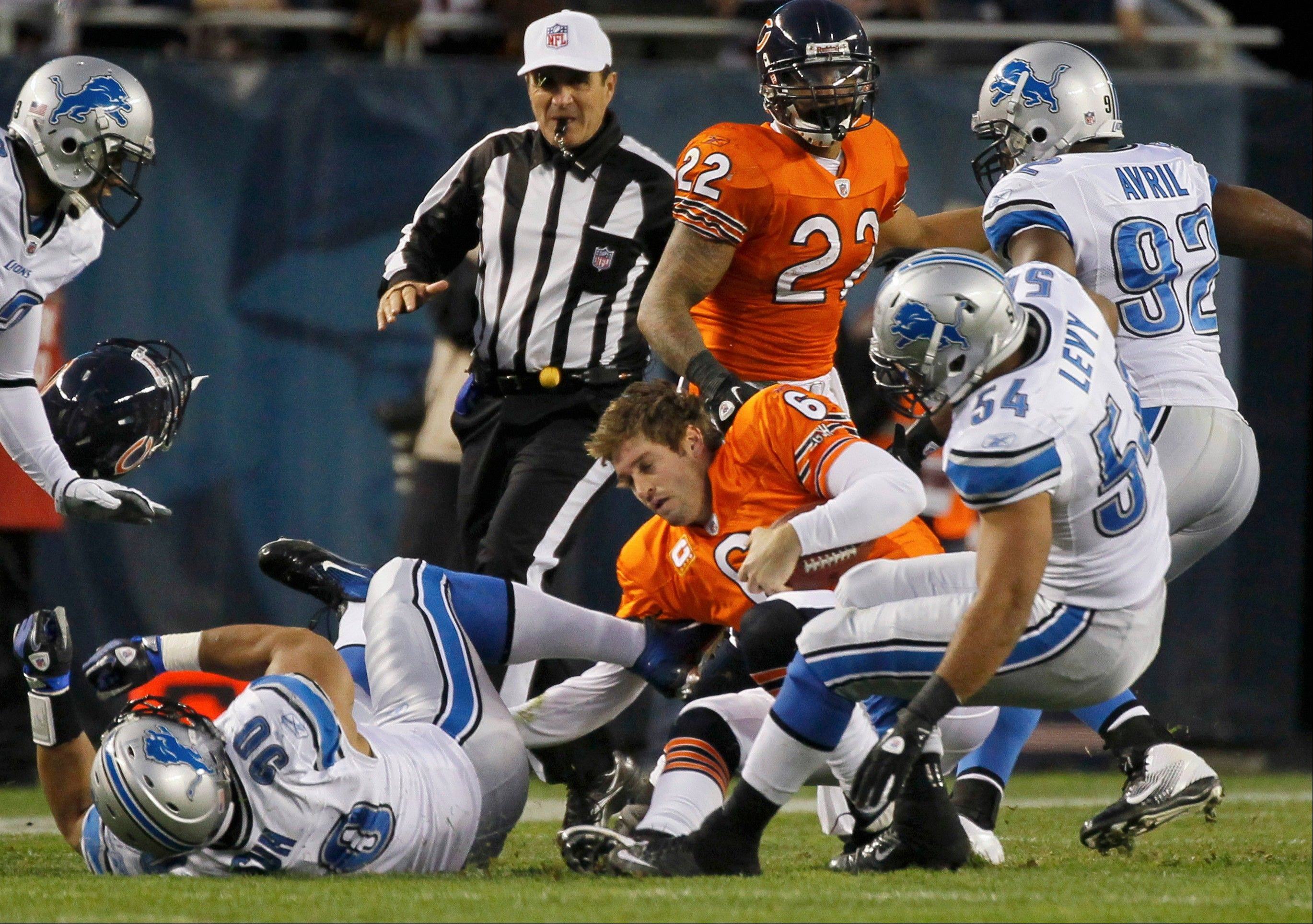 Chicago Bears quarterback Jay Cutler (6) loses his helmet as he is sacked by Detroit Lions defenders Ndamukong Suh (90), DeAndre Levy (54), and Cliff Avril (92) in the first half of an NFL football game, Sunday, Nov. 13, 2011, in Chicago.
