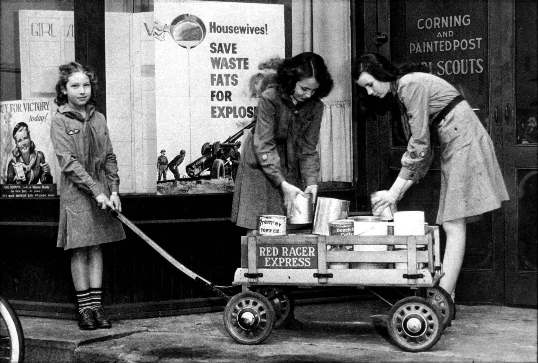 Each generation of Girl Scouts is taught to help others. In the 1940s, Girl Scouts, in front of a Girl Scout Council office, load a wagon with canned goods in support of the war effort.