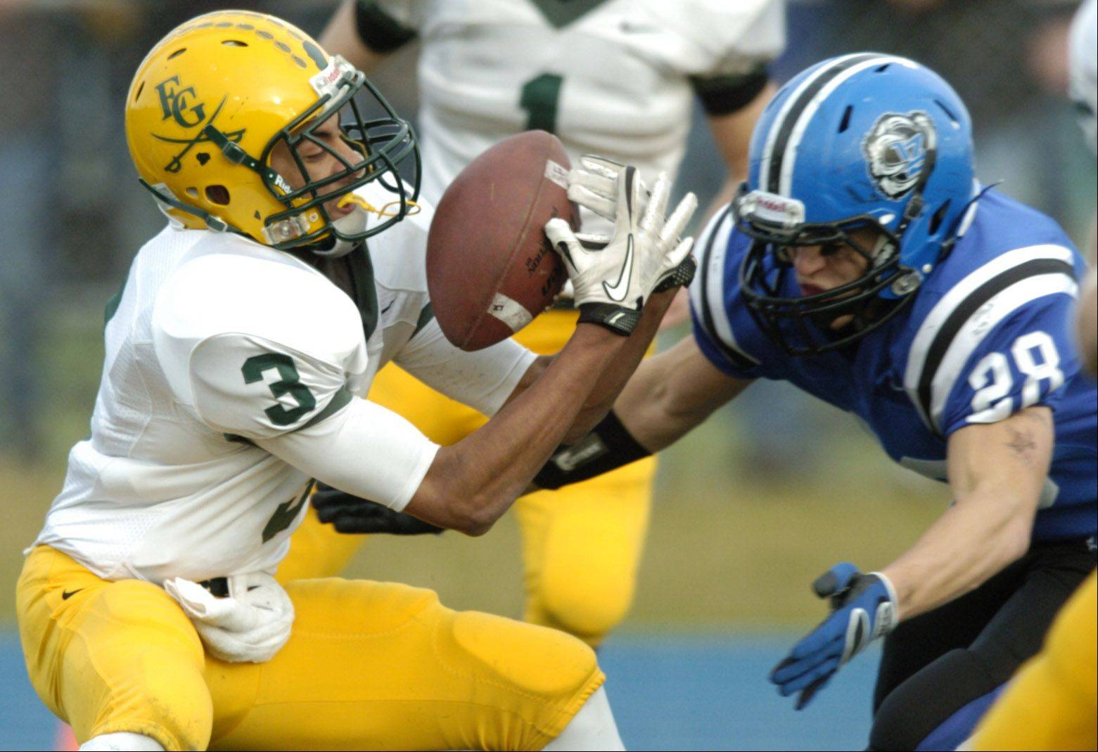 Elk Grove's Kishan Patel nearly fumbles the ball but recovers as Lake Zurich's Blake Moskal closes in.