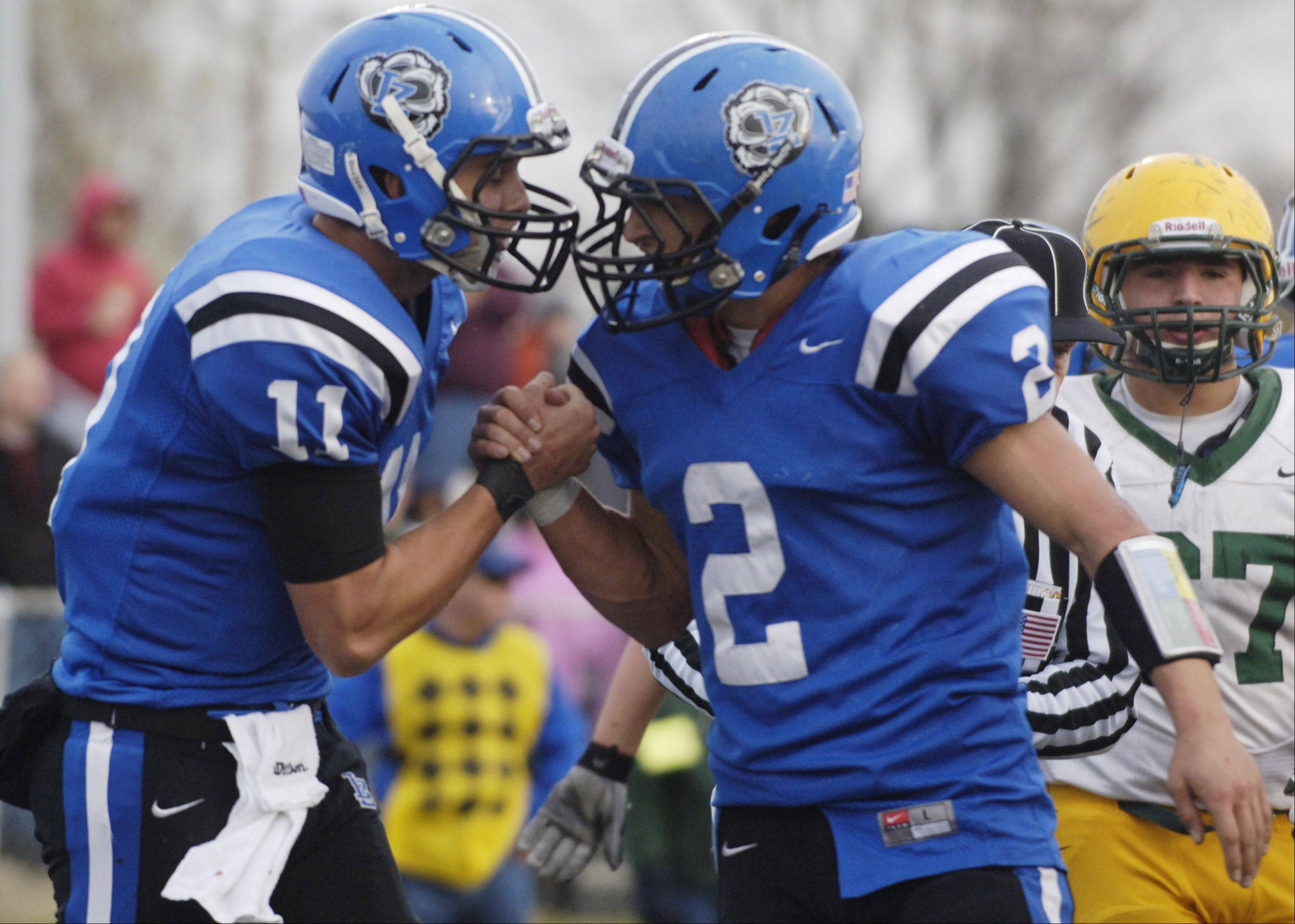 Lake Zurich's Steven Kuhn, left, celebrates his fourth-quarter touchdown with teammate Mike Shield during Saturday's 17-10 Class 7A football win over Elk Grove.
