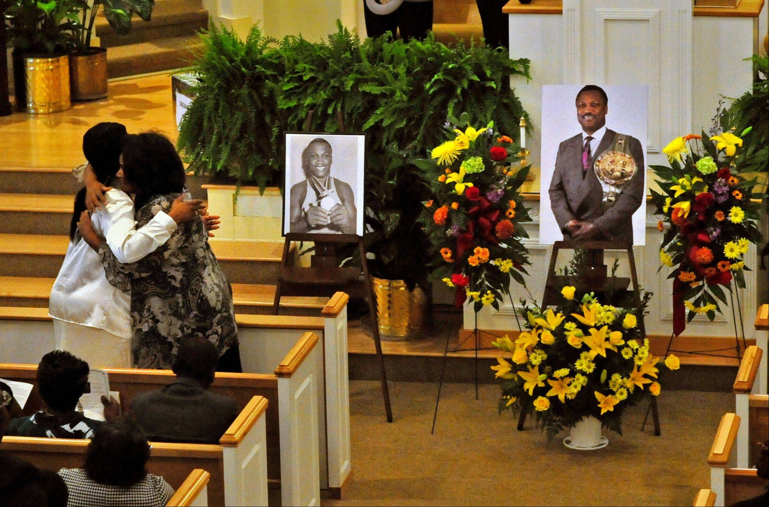 Joe Frazier's daughter Jacqui Frazier Lyde, left, and niece Dannette Frazier, right, hug Wednesday during a memorial service for the former heavyweight boxing champion at the Bethesda Christian Fellowship Temple in St. Helena Island, S.C. Frazier died earlier this month from liver cancer. He was 67.