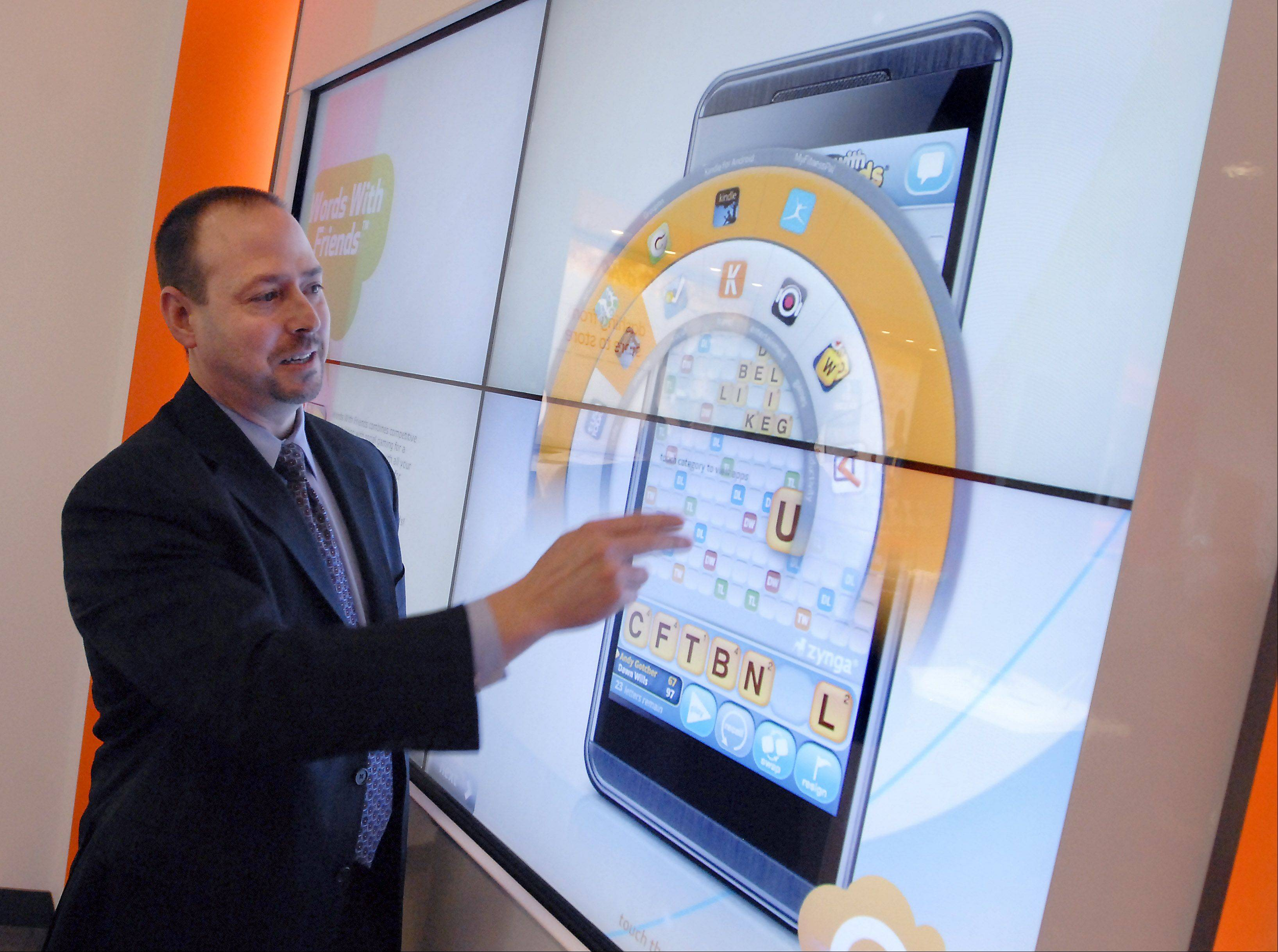Dave Fine, vice-president/general manager for Illinois and Wisconsin for AT&T, demonstrates a new touch screen wall that shows customers how to utilize apps at the new AT&T Innovation Center in Arlington Heights. Below, Lourdes Burson, director of store design for AT&T, points out features of the store.