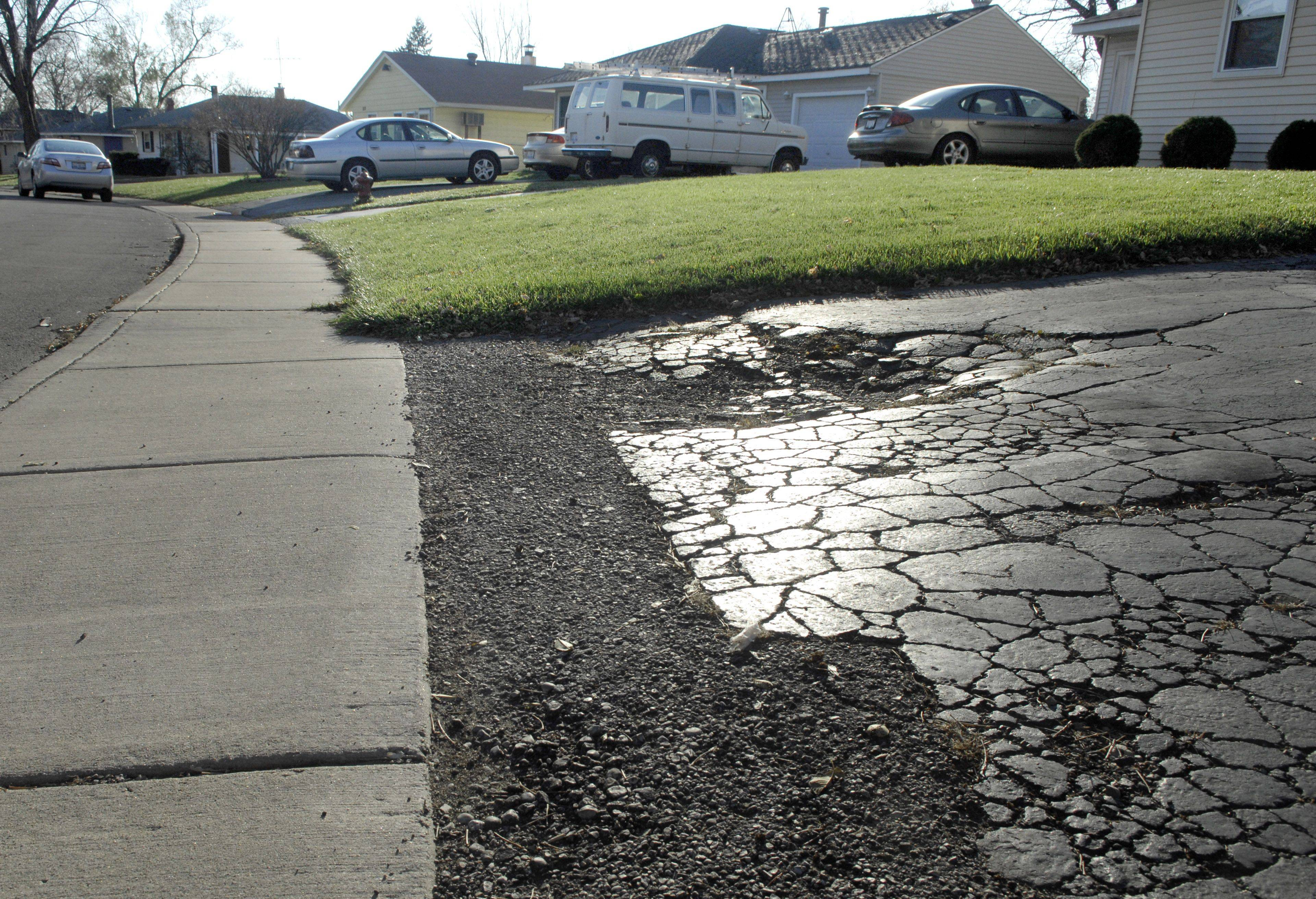 A driveway on Chippewa Circle in Carpentersville has fallen into disrepair. Carpentersville trustees are considering whether to extend the June 2012 deadline on required driveway repaving.