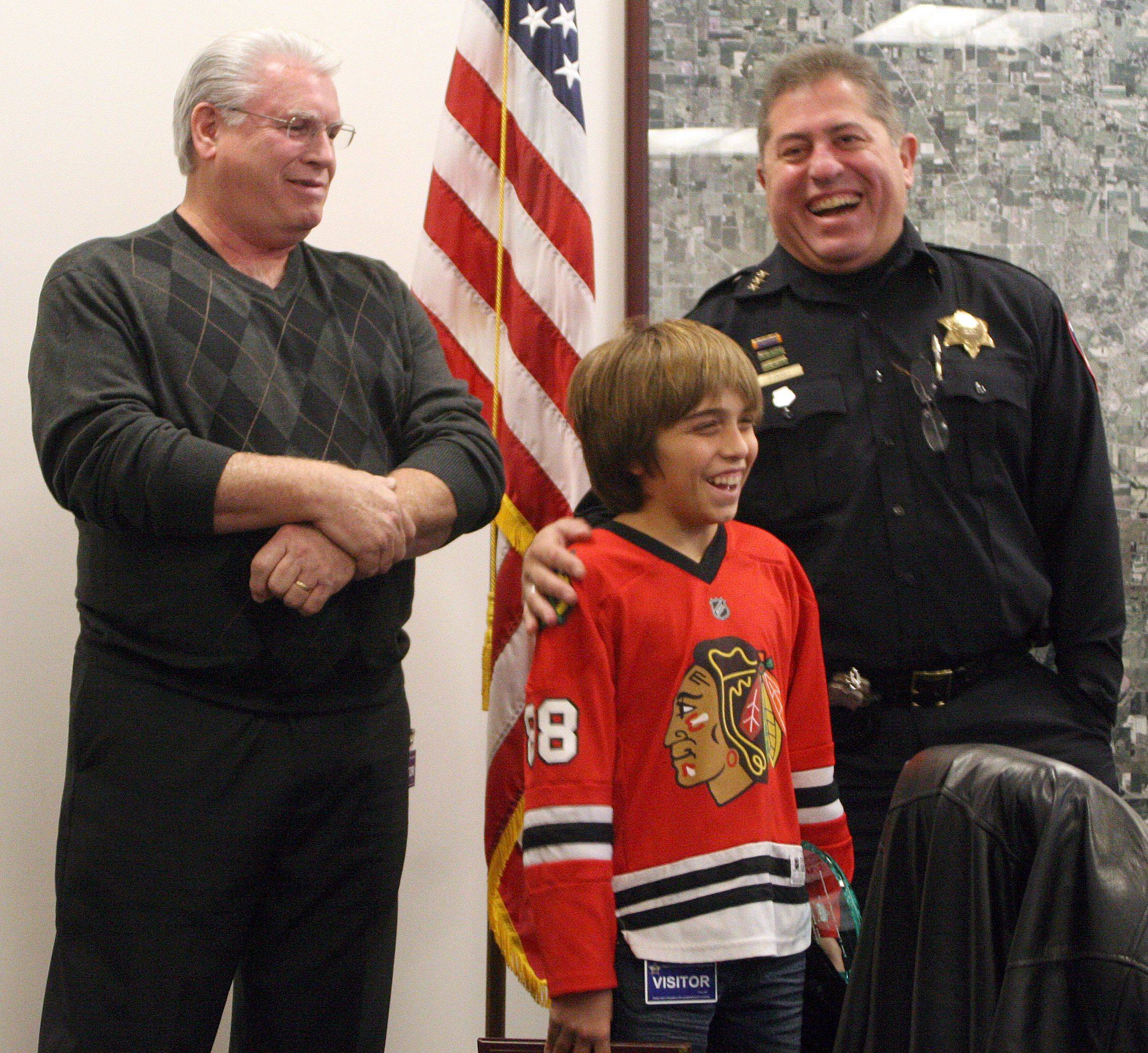 Richard Ebey of Montgomery, Cole Rutter, 13, of Sugar Grove, and Kane County Sheriff Pat Perez share a laugh after Cole was awarded the 2011 Roscoe Ebey Award at the sheriff's office Thursday. The annual award is bestowed based on outstanding performance in the community. Cole has raised large sums of money for The Children's Tumor Foundation.
