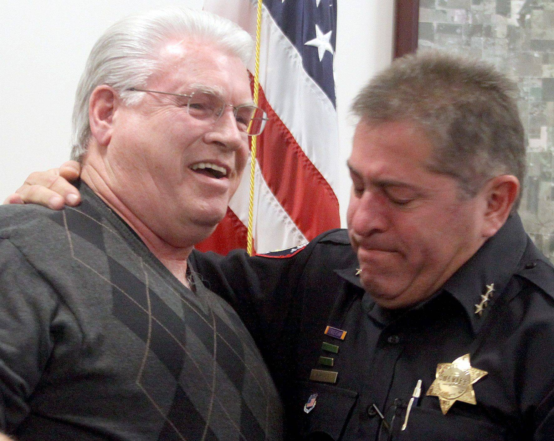 Richard Ebey and Kane County Sheriff Pat Perez share a moment Thursday at the sheriff's office after Ebey offered a special edition of the Roscoe Ebey Award to Perez in honor of the kindness, care and guidance the sheriff's department has displayed in the years since Richard's father, Roscoe, was killed during a 2007 Aurora Township robbery.