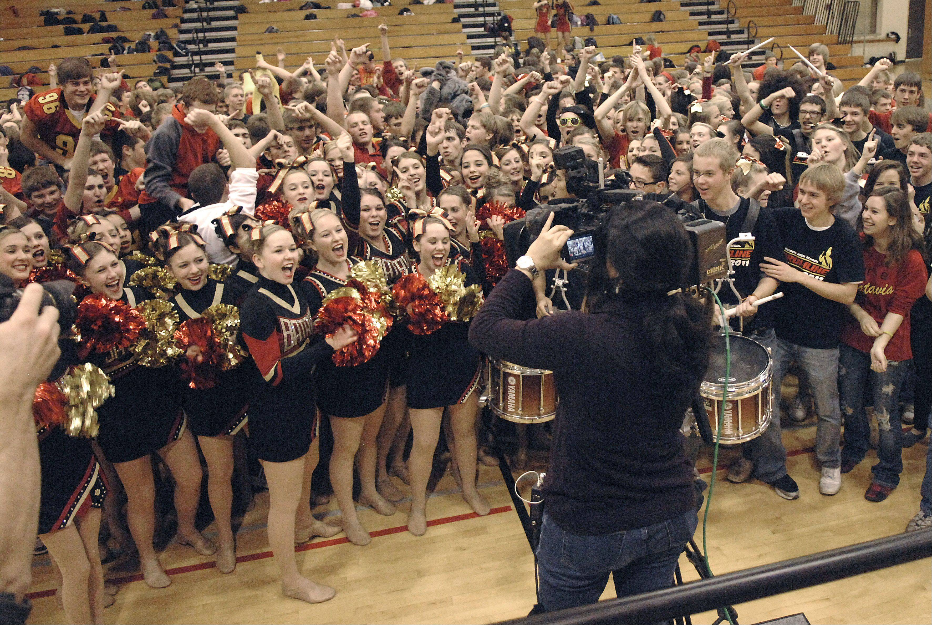 "NBC5 camerawoman Maria Ruiz is swarmed by students after they empty out of the bleachers and onto the floor during a live shot for NBC5's taping of ""Prep Destination of the Week"" Friday at Batavia High School."