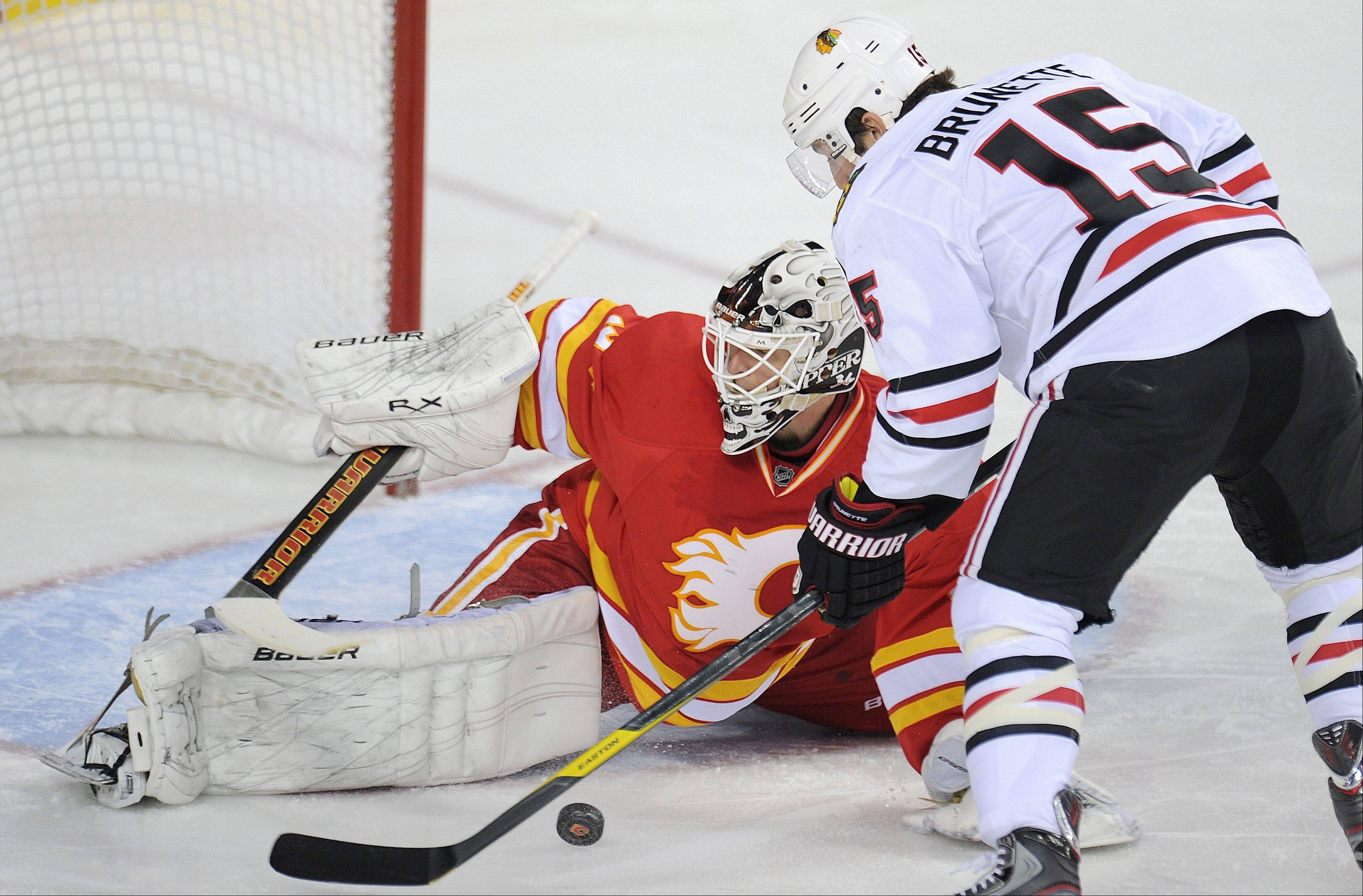 The Hawks' Andrew Brunette, right, has a shot stopped by Flames goalie Mikka Kiprusoff during the second period Friday.