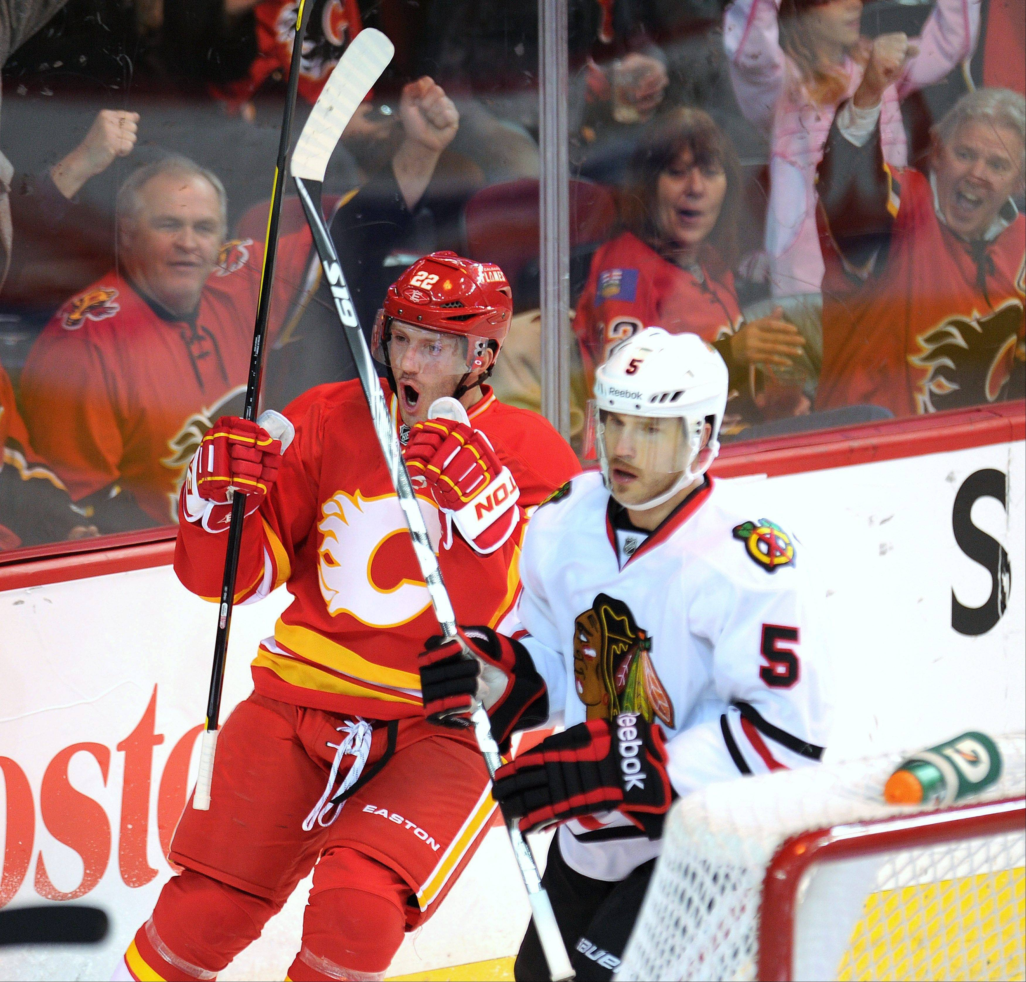 Calgary Flames' Lee Stempniak, left, celebrates a goal as he passes Chicago Blackhawks' Steve Montindor during the first period of an NHL hockey game, Friday, Nov. 18, 2011, in Calgary, Alberta.