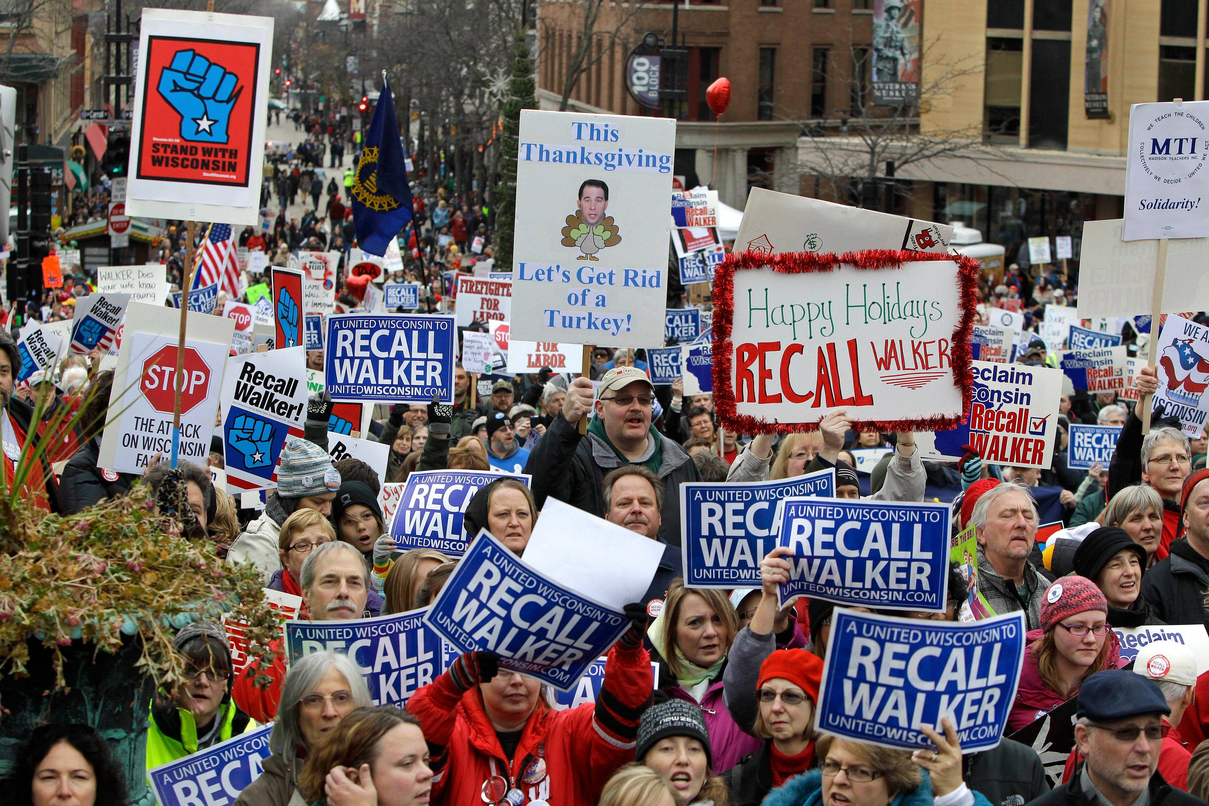 "Colorful signs, recall petitions and blunt messages are displayed at the ""We Are Wisconsin"" rally Saturday. The rally to recall Gov. Scott Walker drew tens of thousands of marchers to Madison."