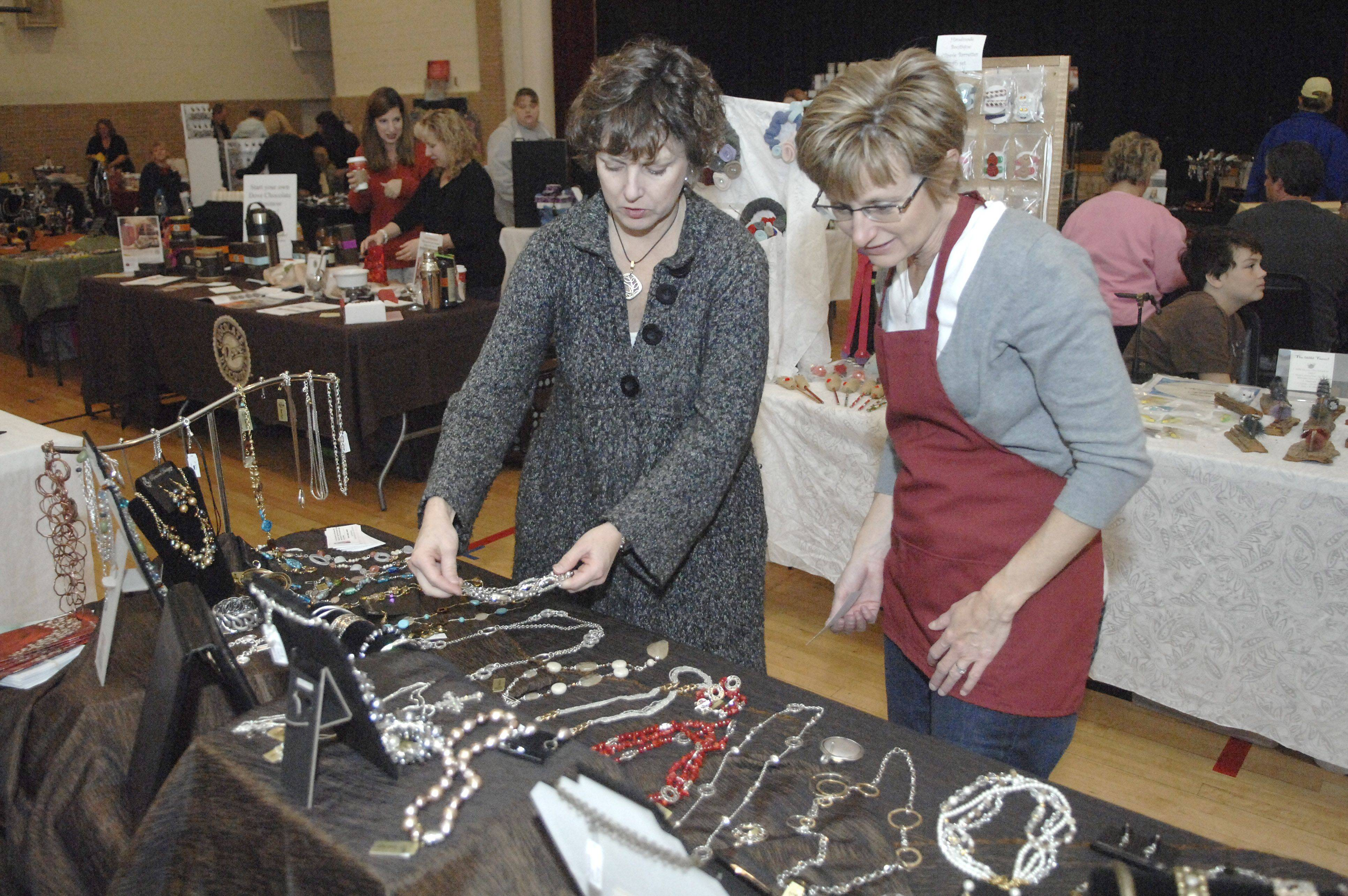 Premier Designs jewelry vendor Carol Abrams helps shopper Jamie Hanson of Batavia browse a large selection of affordable jewelry at the third annual MALLternative craft and vendor show Saturday in the Bethany Ministry Center in Batavia.