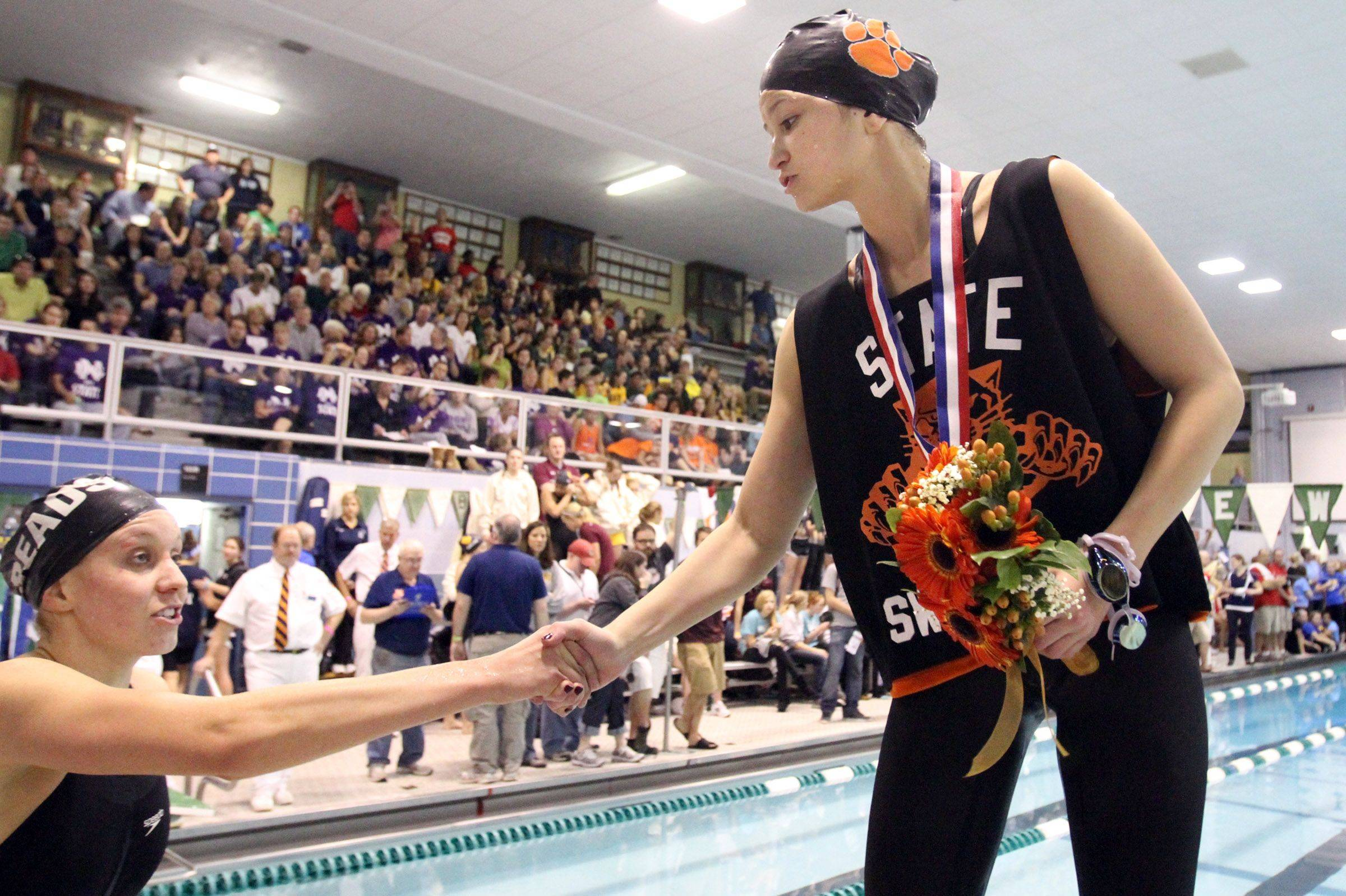 Libertyville's Morgan Dickson, right, placed sixth gets a hand from Rosary's Emily Launer, who placed fourth in the 500-yard freestyle at IHSA state championships in Winnetka on Saturday, November 19th.