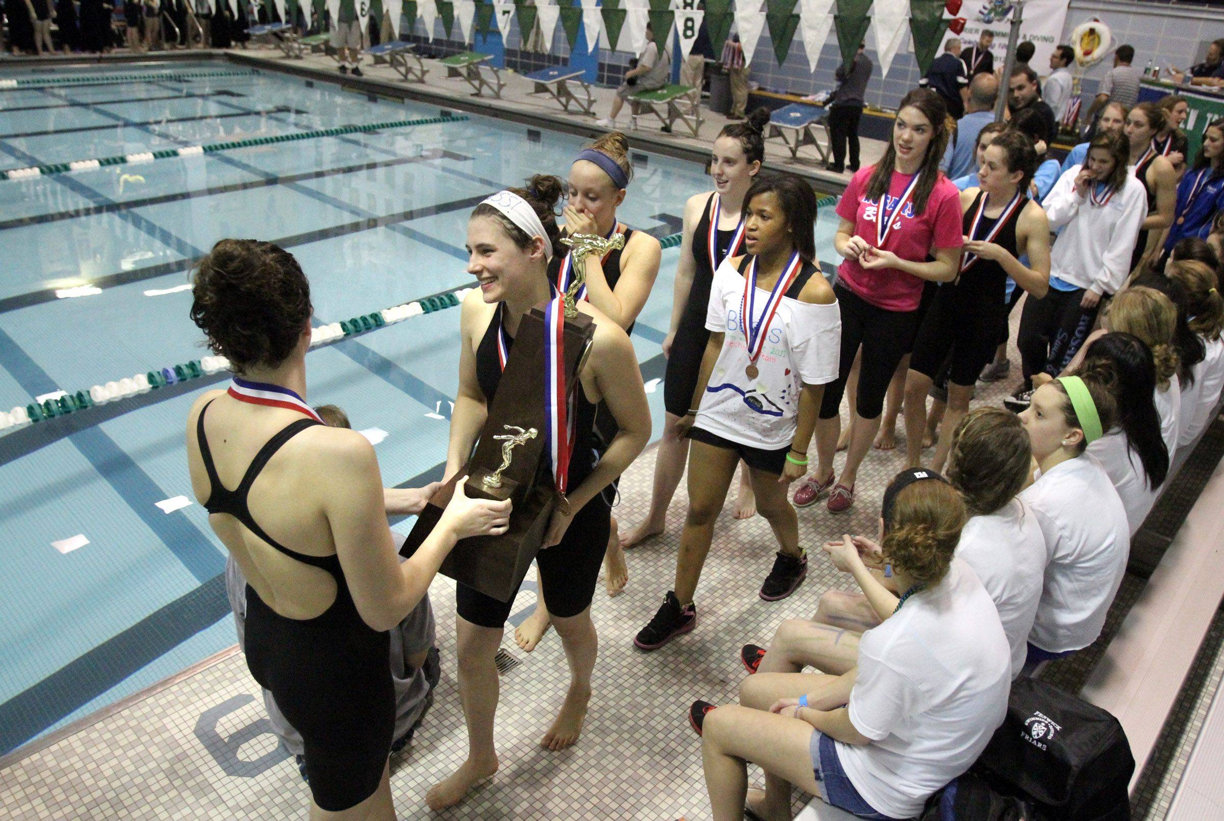 Rosary walks around the pool with the third place team trophy at the IHSA state championships in Winnetka on Saturday, November 19th.