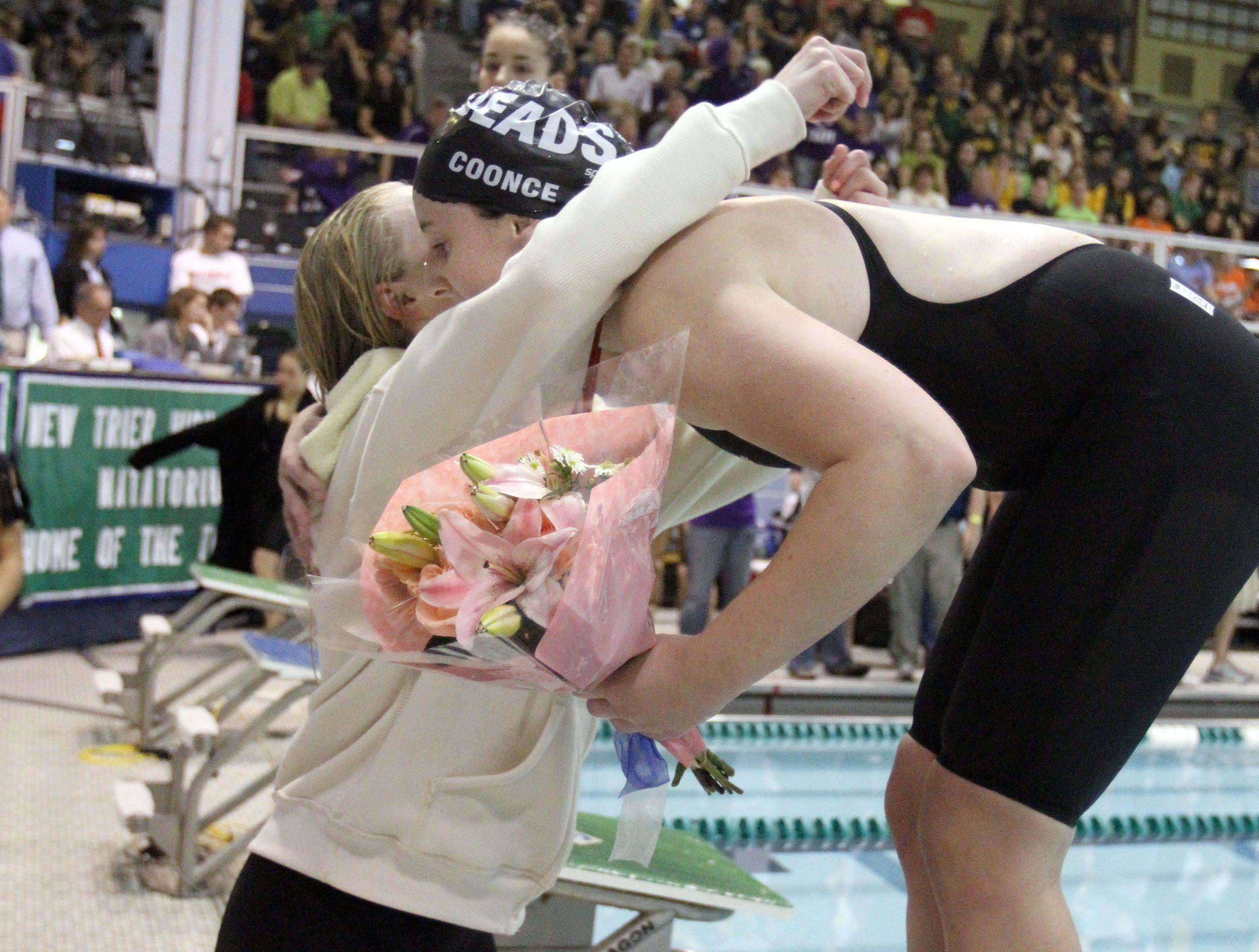 Loyola Academy's Michelle Garland, of Grayslake, left, placed third, gives Rosary's Molly Coonce a hug as she placed fifth in the 100-yard breaststroke at IHSA state championships in Winnetka on Saturday, November 19th.
