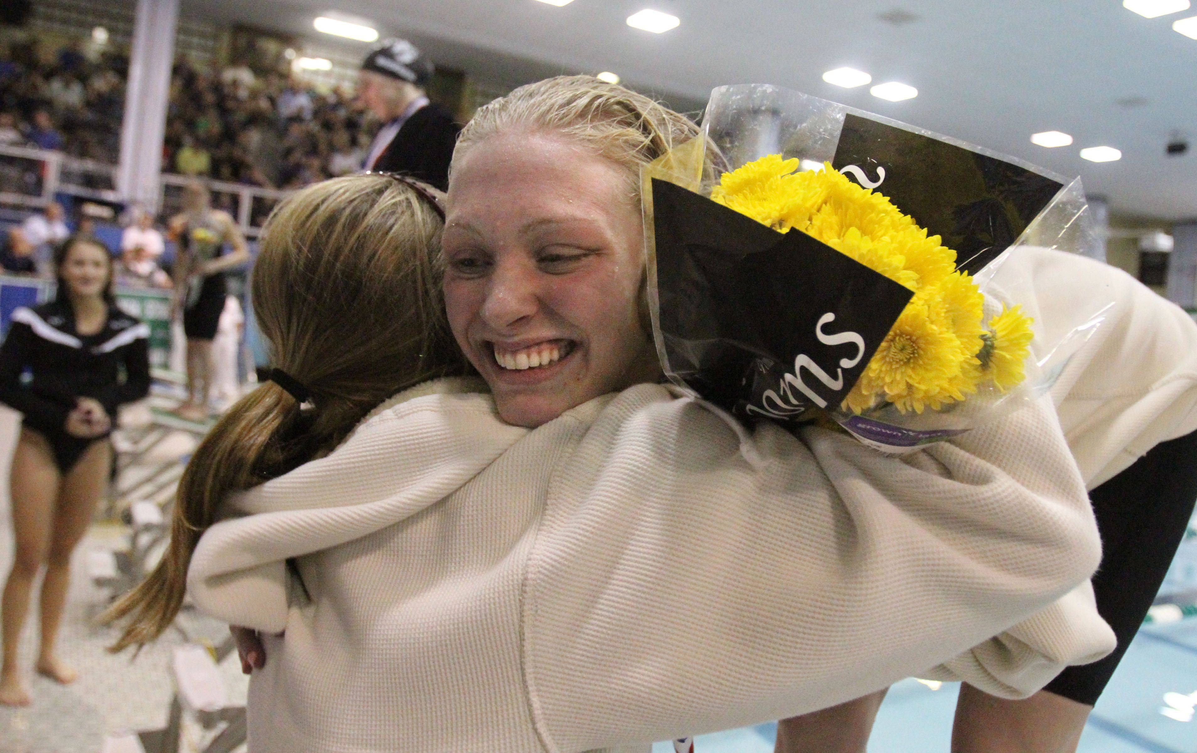 Loyola Academy's Michelle Garland, of Grayslake, gets a hugs as she finished third in the 100-yard breaststroke at IHSA state championships in Winnetka on Saturday, November 19th.