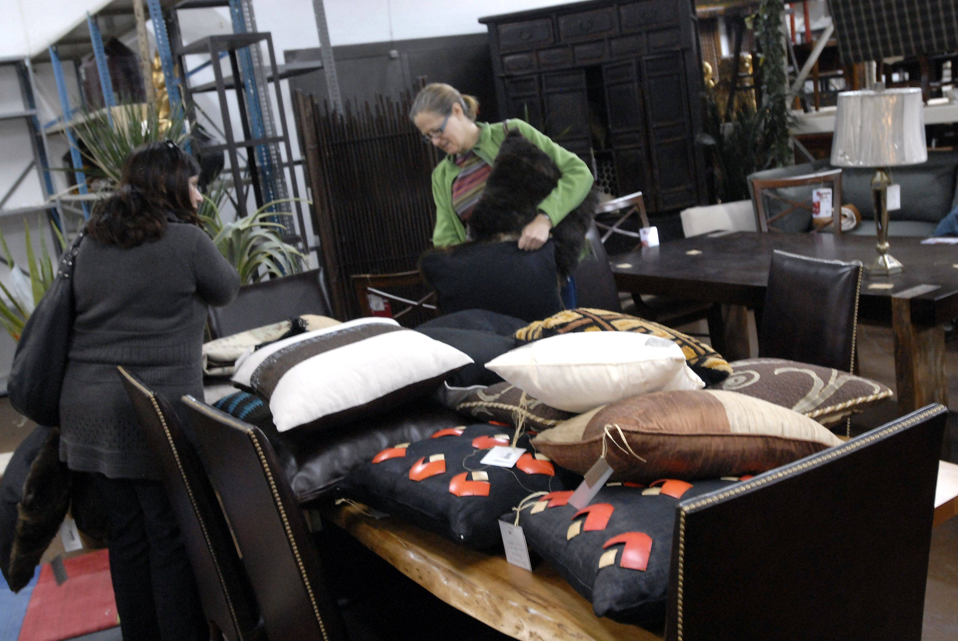 Ana Puga, left, of Carol Stream and Ann Priest of Inverness check out pillows at the sample sale at C.A.I. Design.