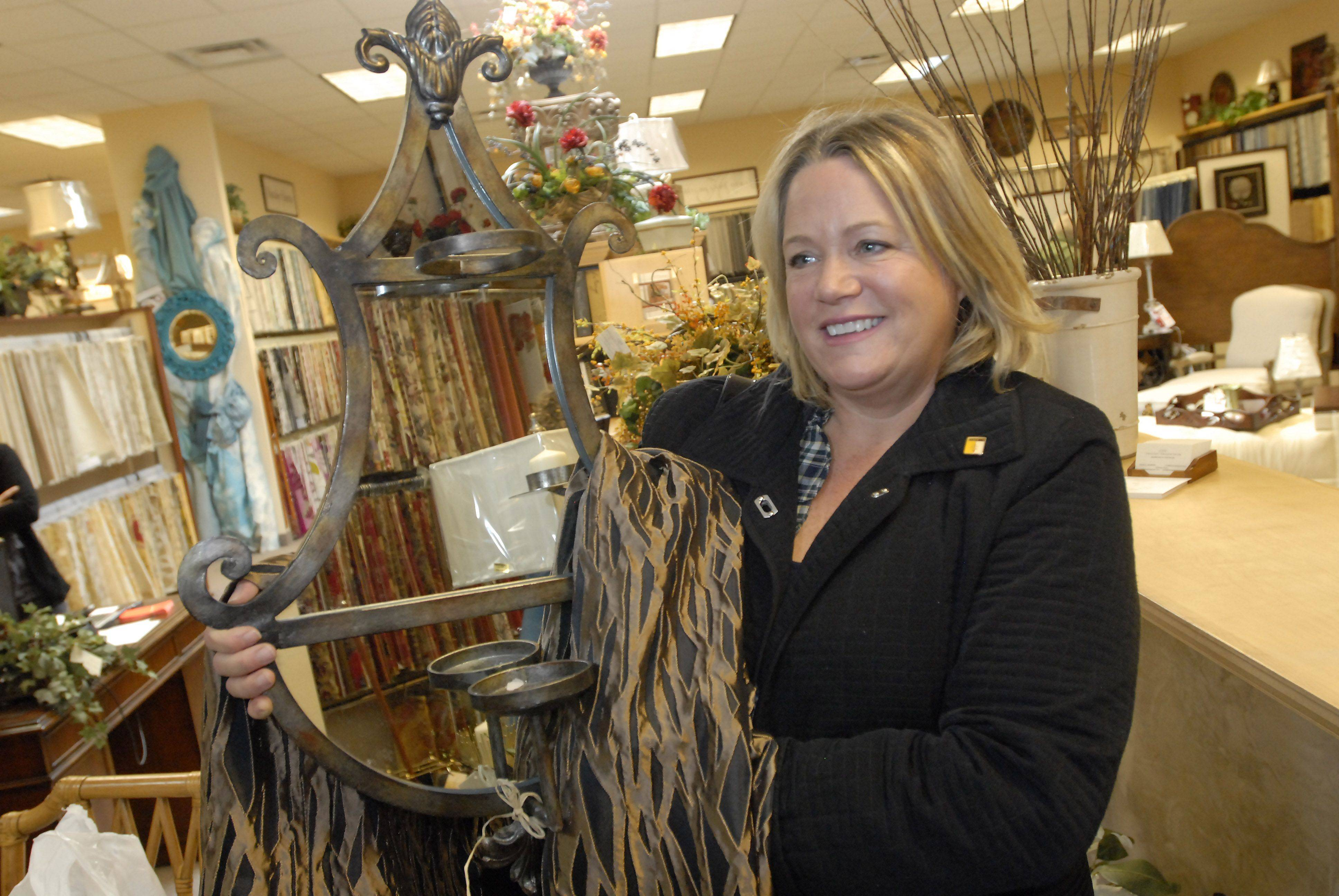 Julie Towers of Palatine shows a mirror and fabric panel that were among her purchases at the Arlington Design Center.