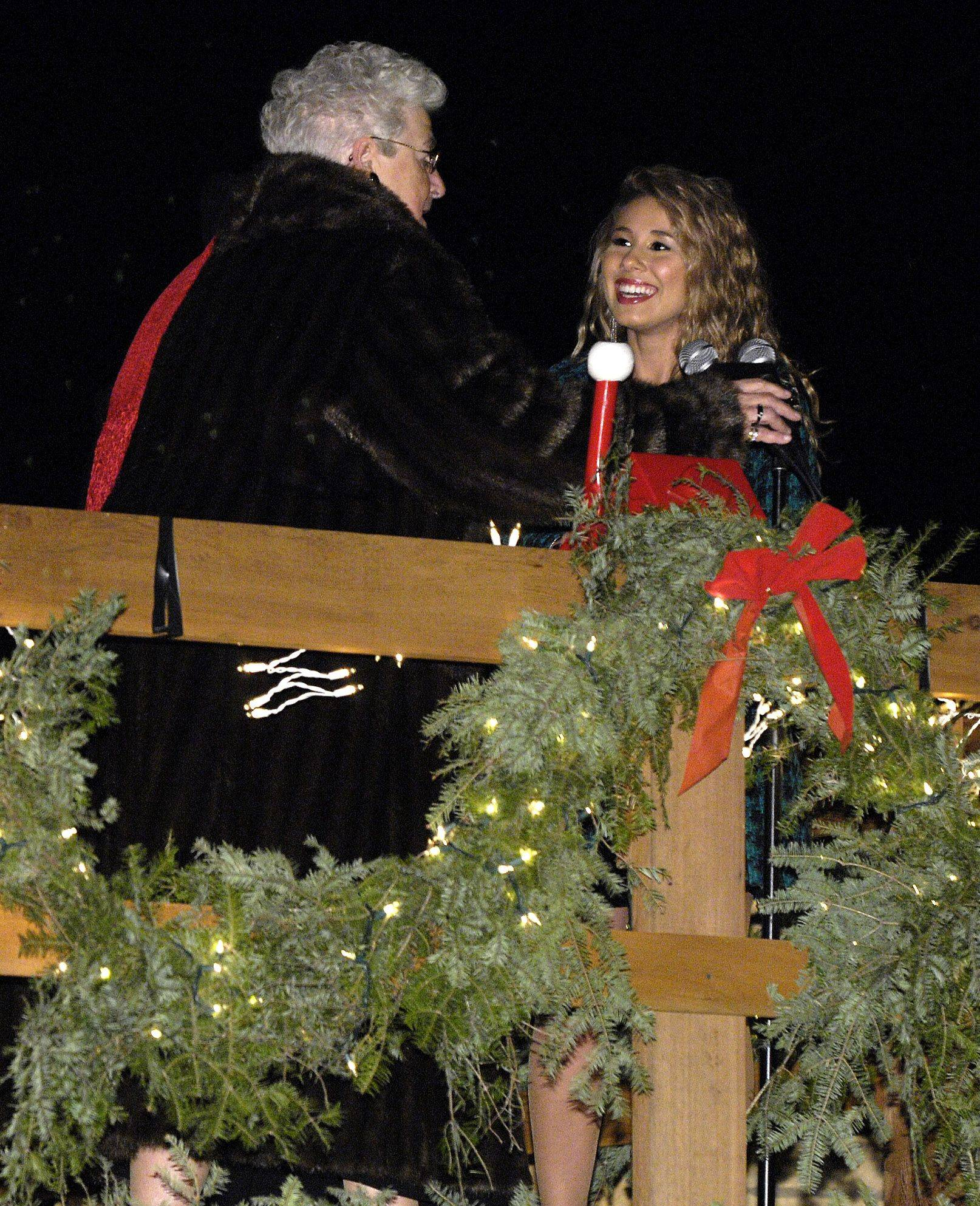 "Wheeling Village President Judy Abruscato and ""American Idol"" finalist Haley Reinhart flip the switch to light up the Christmas lights Sunday evening at Friendship Park in Wheeling."