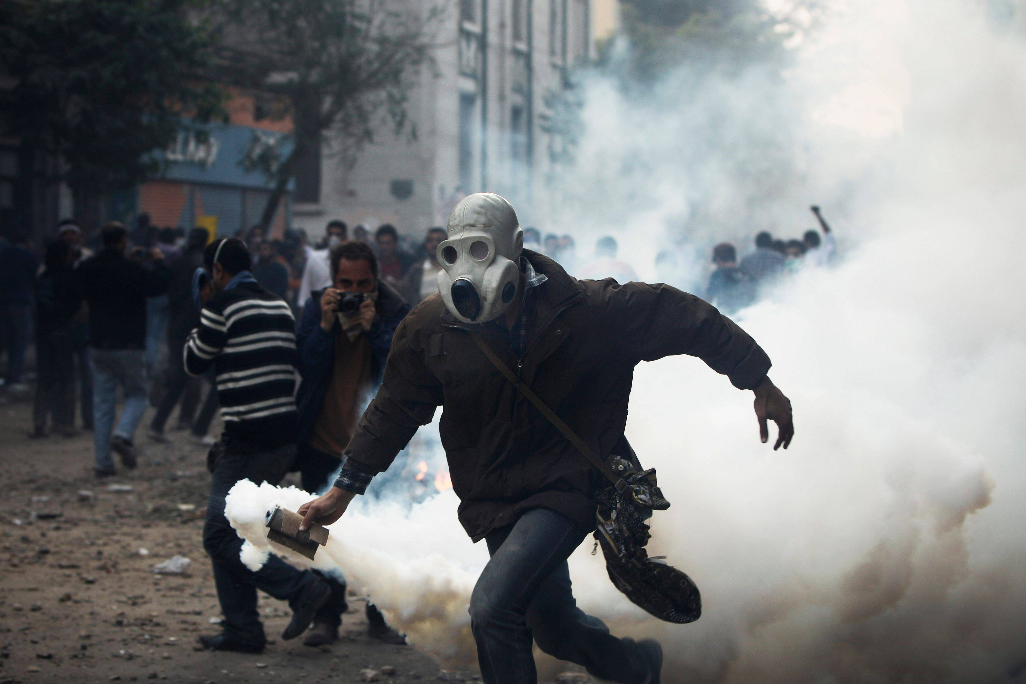 A protester throws a gas canister towards Egyptian riot police, near the interior ministry during clashes in downtown Cairo, Egypt, Sunday.